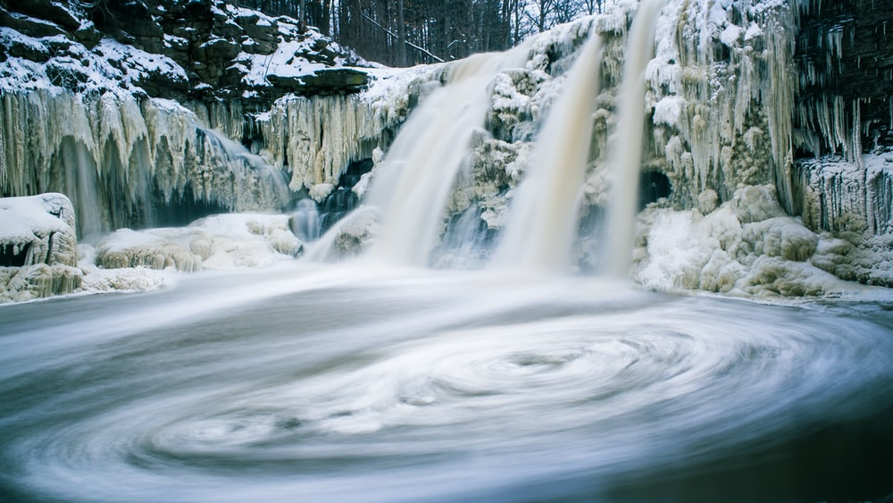 timelapse photography of waterfalls with melted snow
