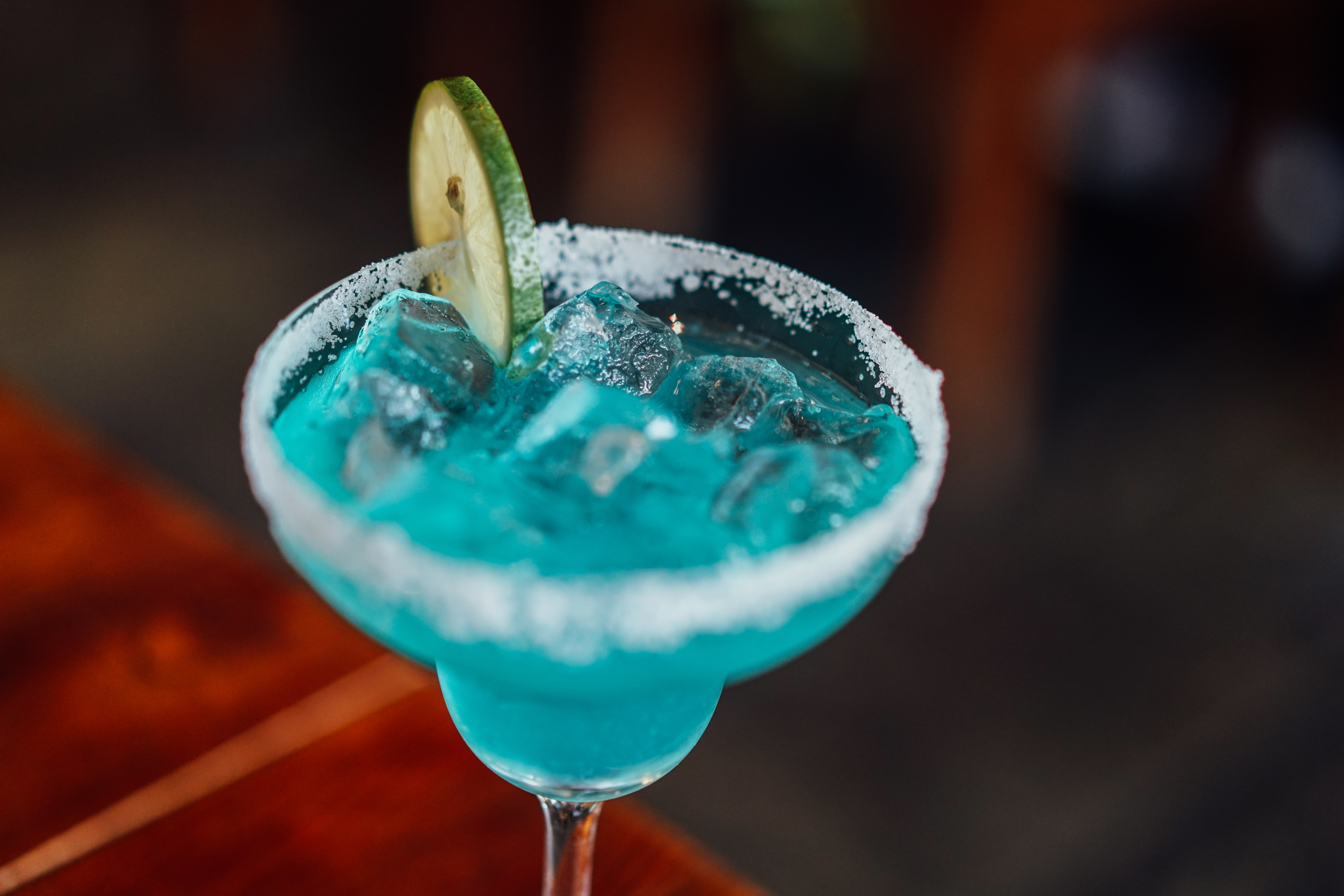 clear margarita glass with cyan liquid and lime slice