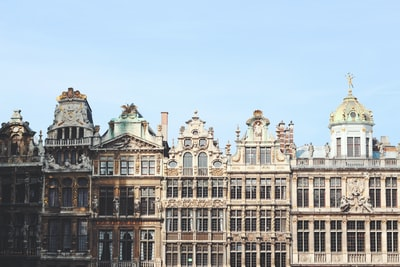gray and brown building under blue sky belgium teams background