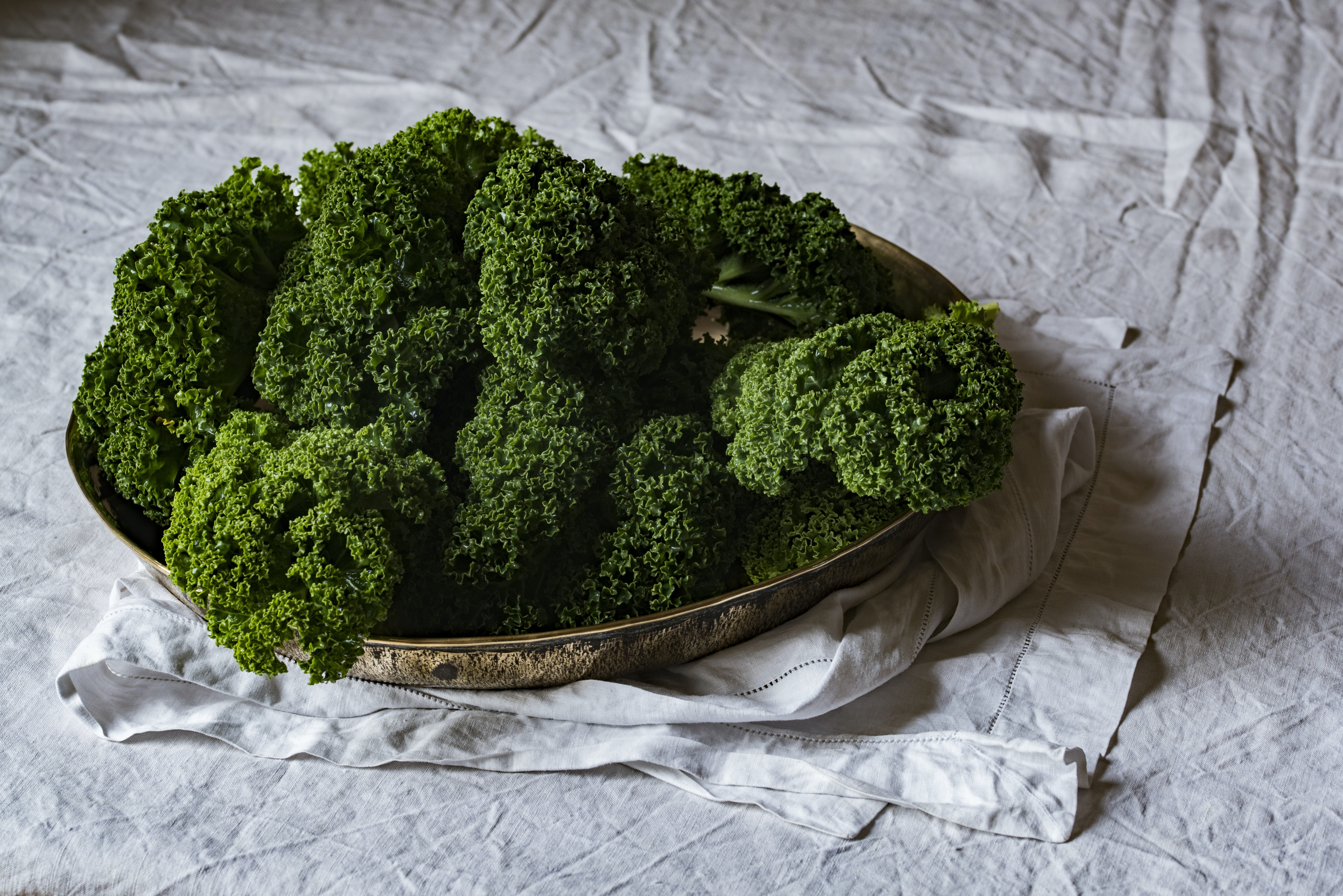 Green kale on a platter on a white tablecloth