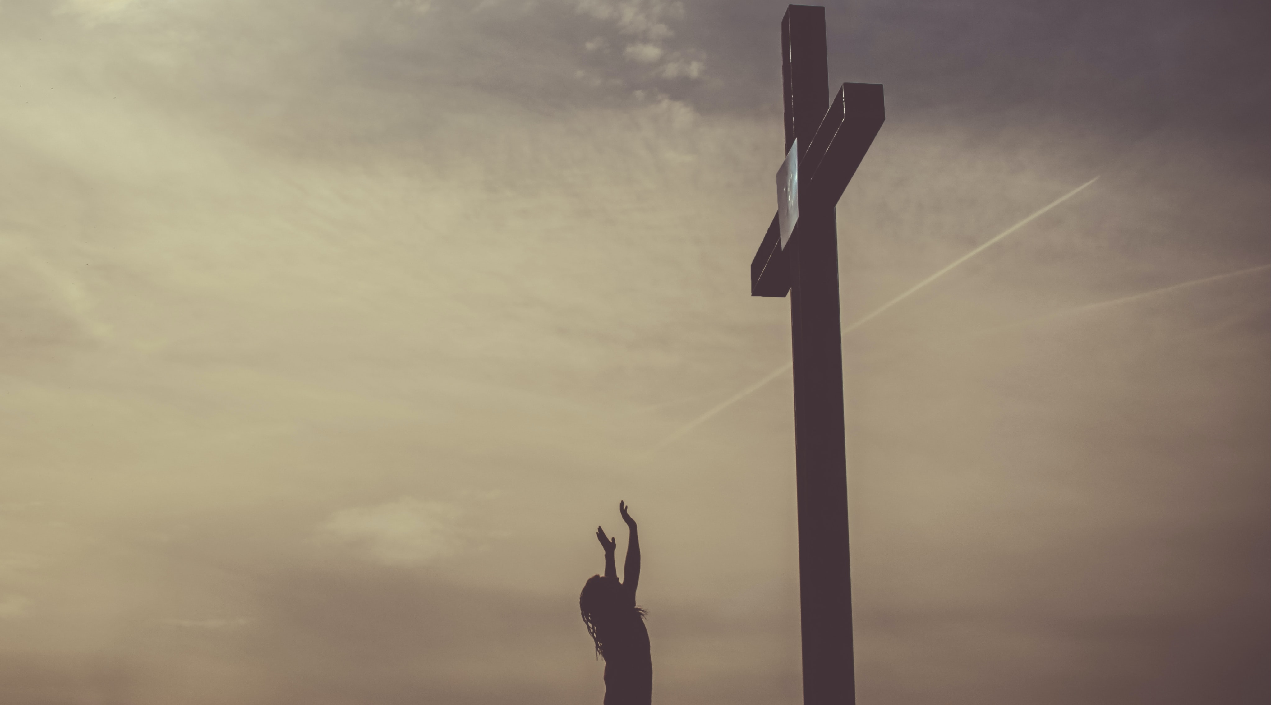 A cross with a cloudy sky background.