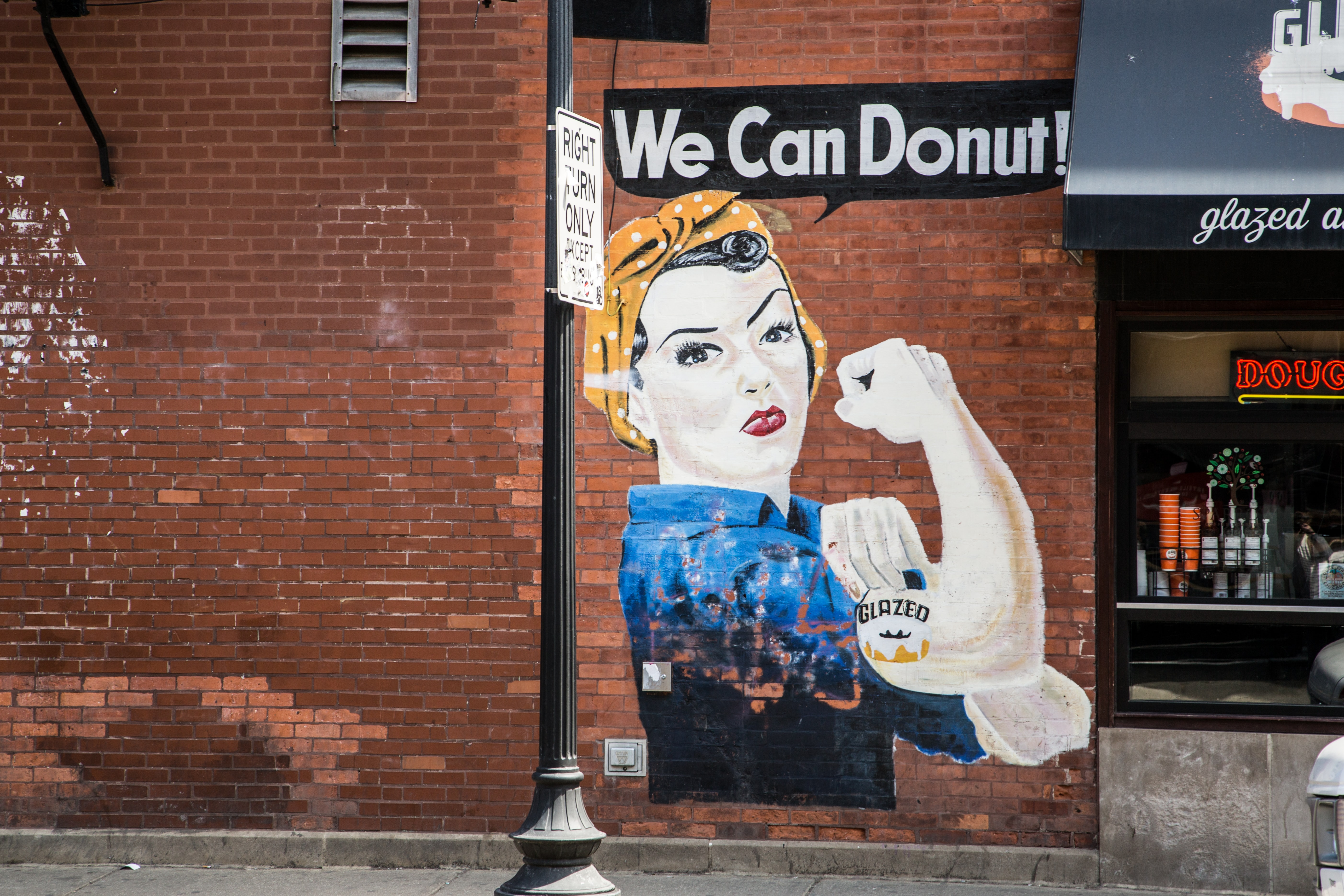 """A feminist meme painted on a wall with the caption, """"We Can Donut!"""""""