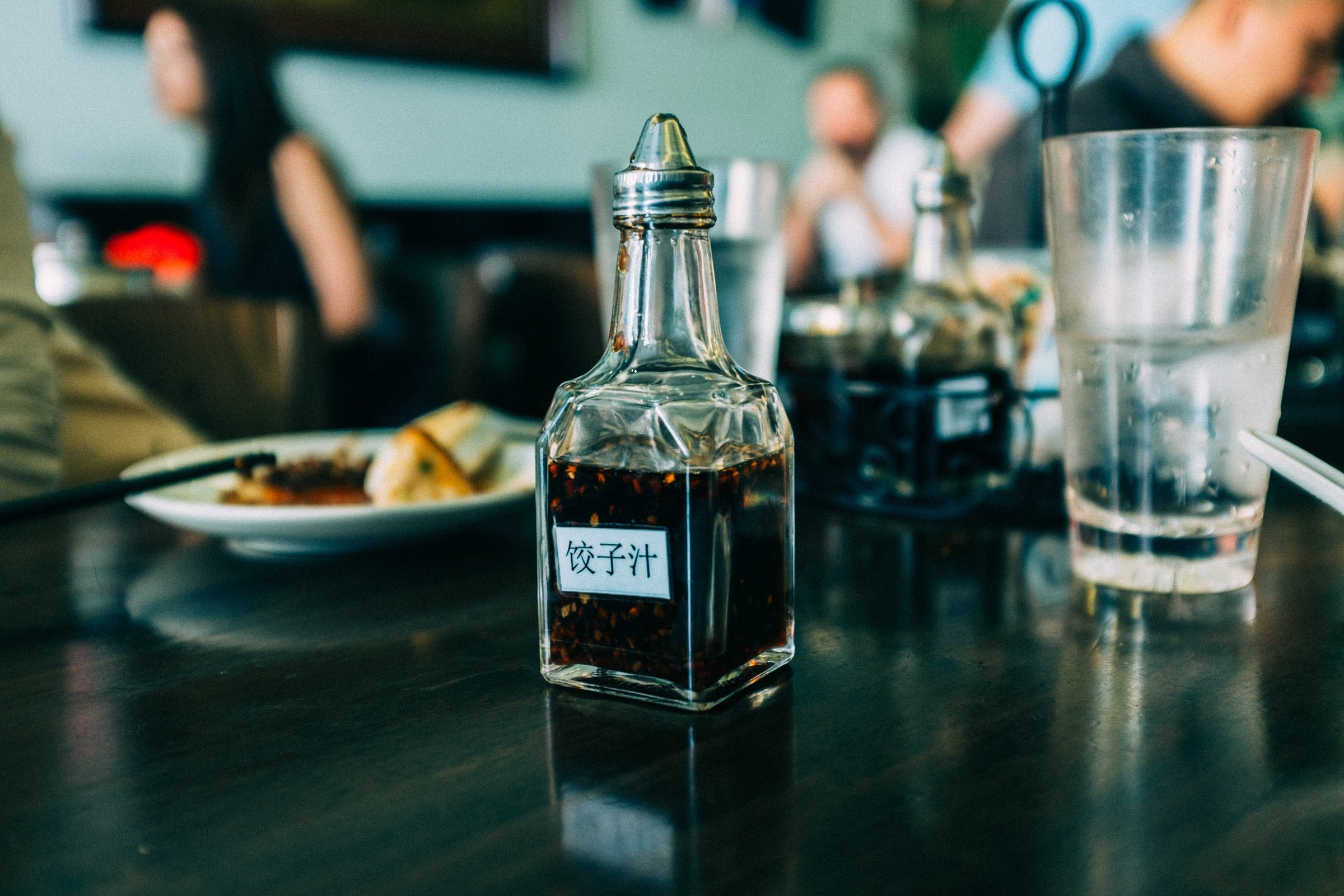 clear glass condiments container on black wooden board
