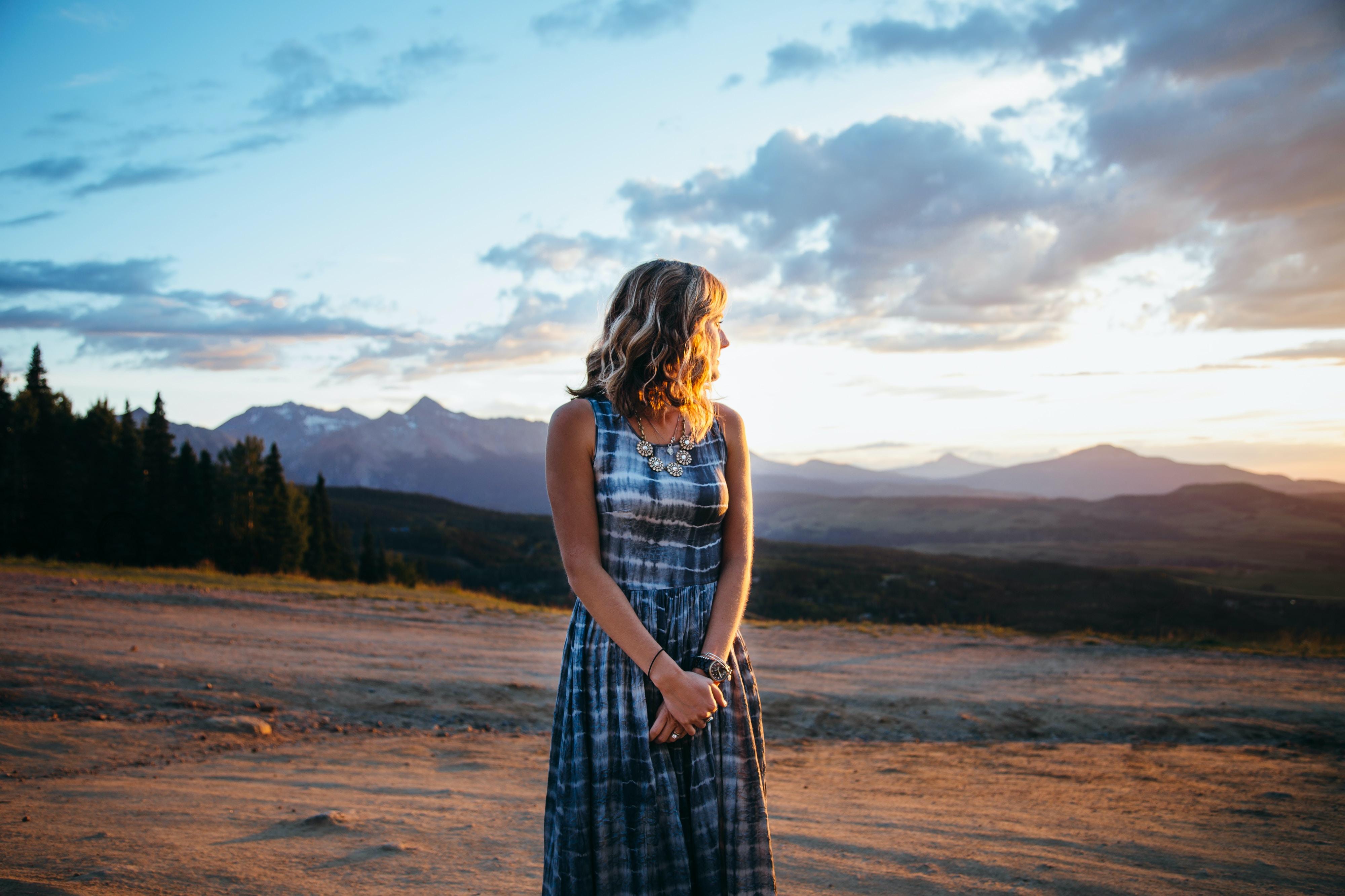 Beautiful Woman in tiedye summer dress with long hair enjoying the golden sun rays in Telluride