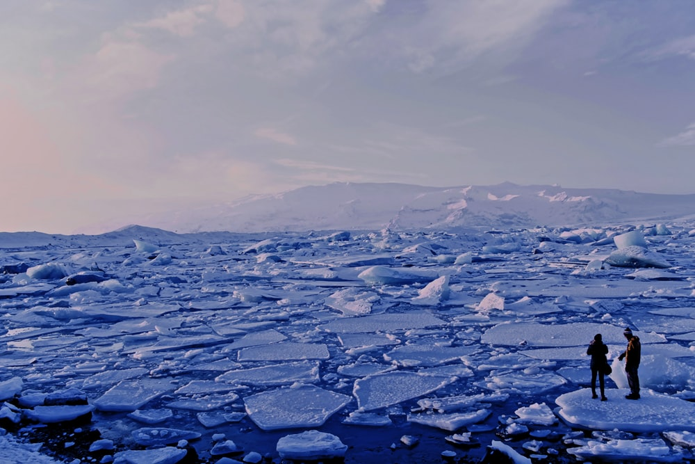man and woman standing cracked sea ice under gray sky