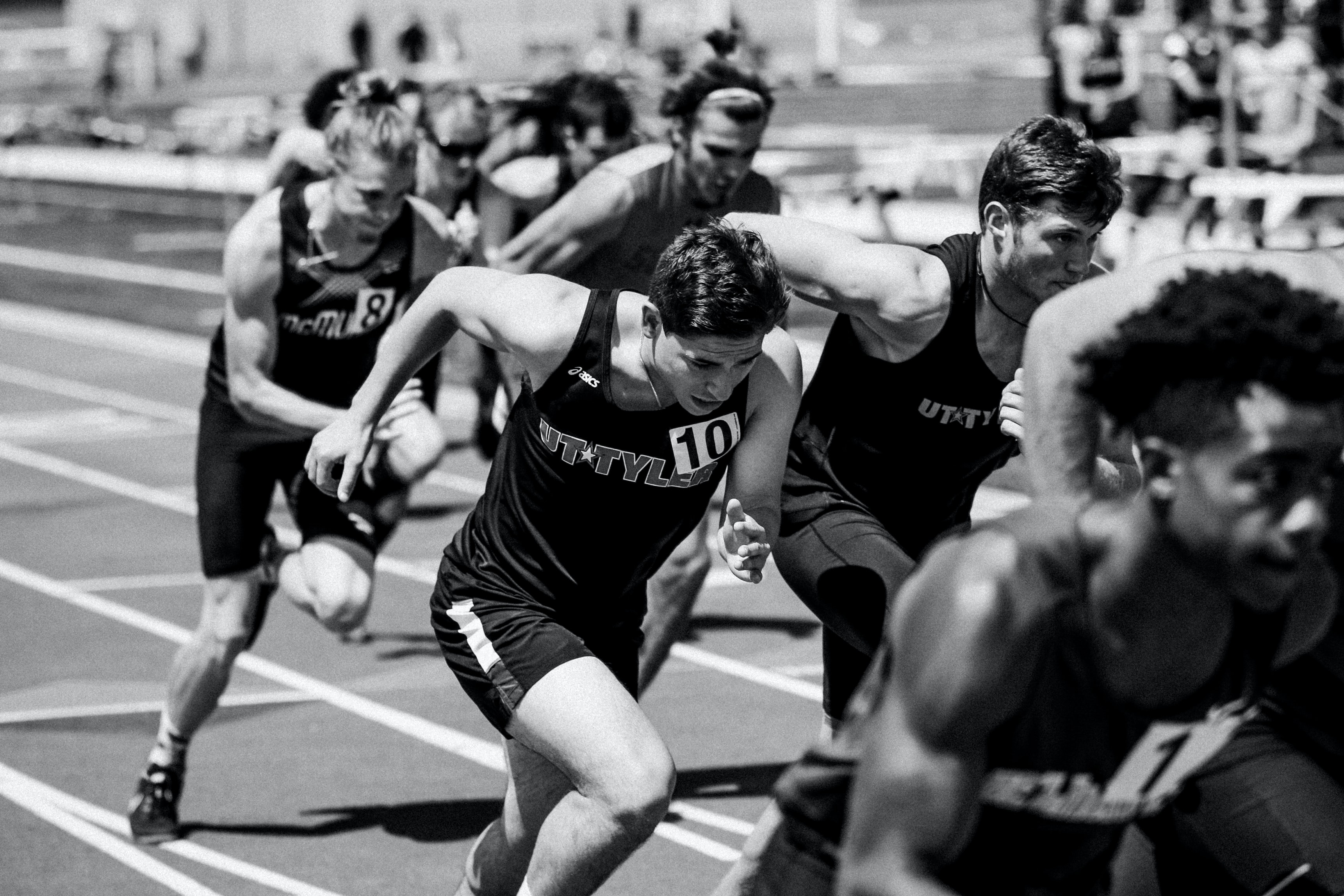 A black and white shot of runners racing on a track