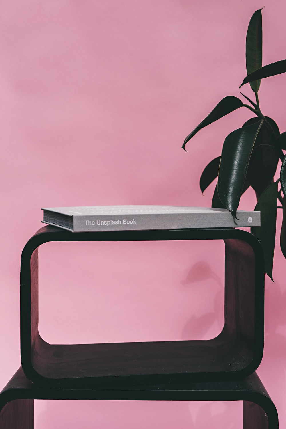 A cube shelf with a book on top, next to an indoor plant.