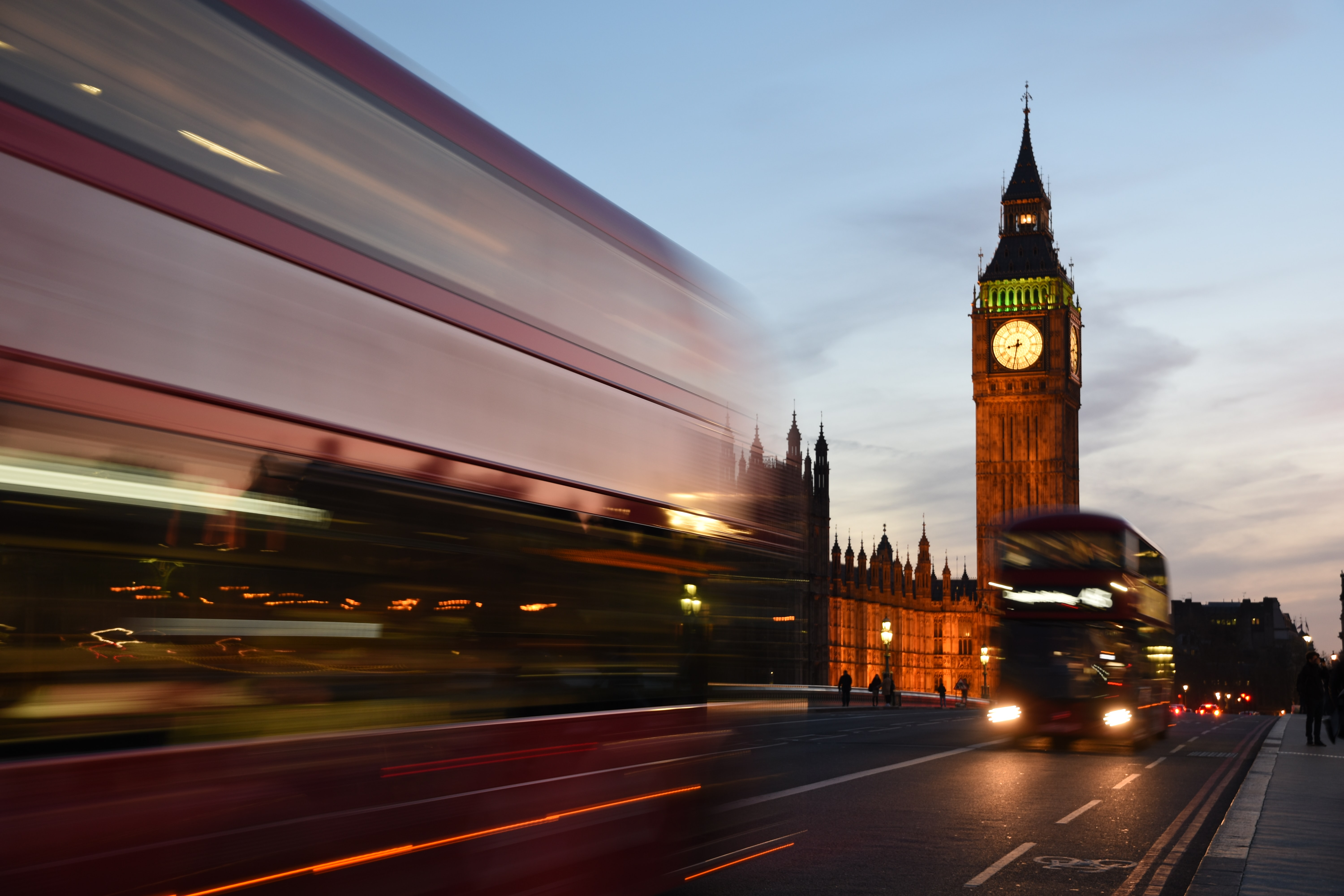 A long-exposure shot of double-decker buses near the Houses of Parliament in London