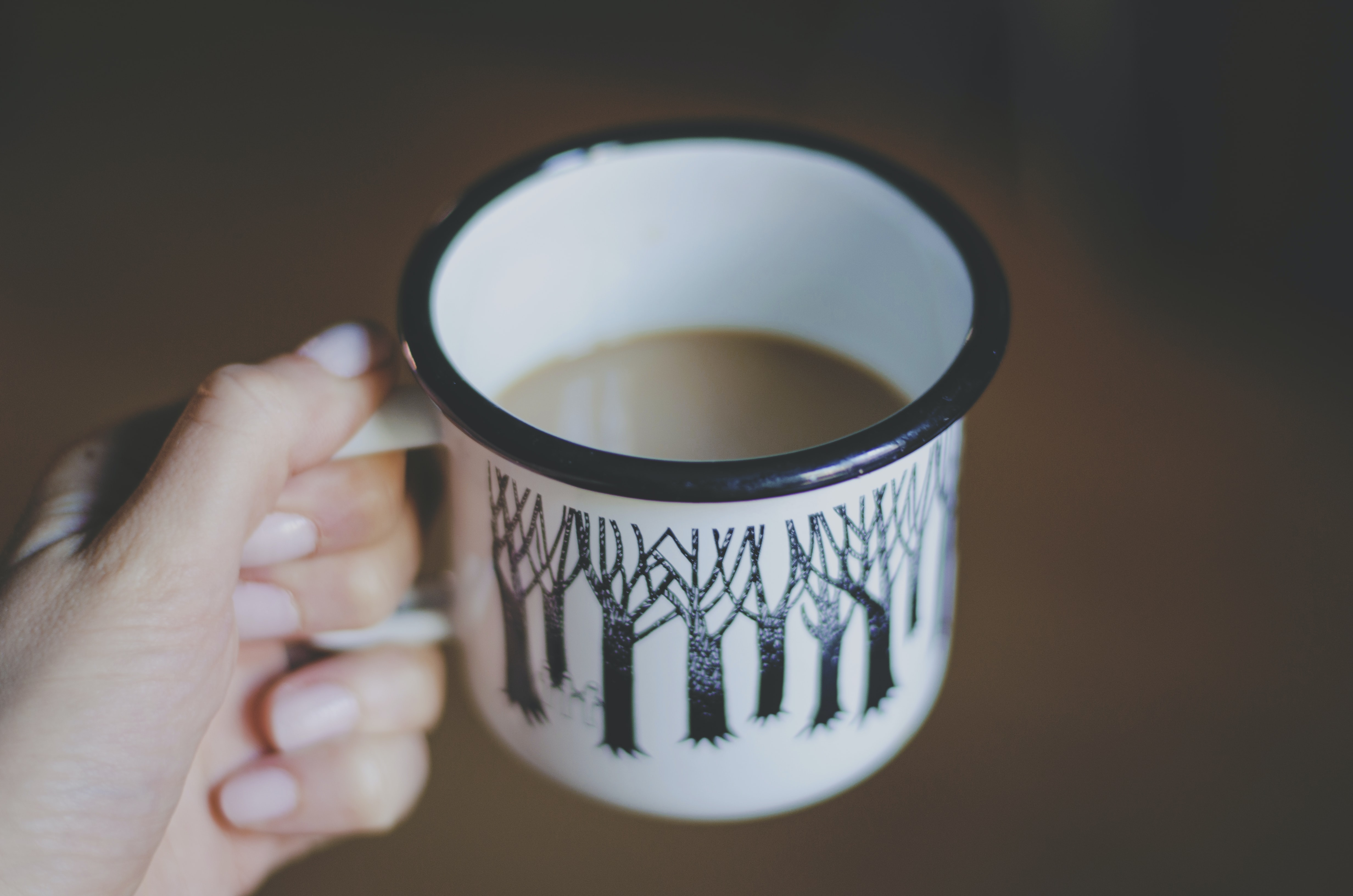 white and black ceramic mug filled with coffee