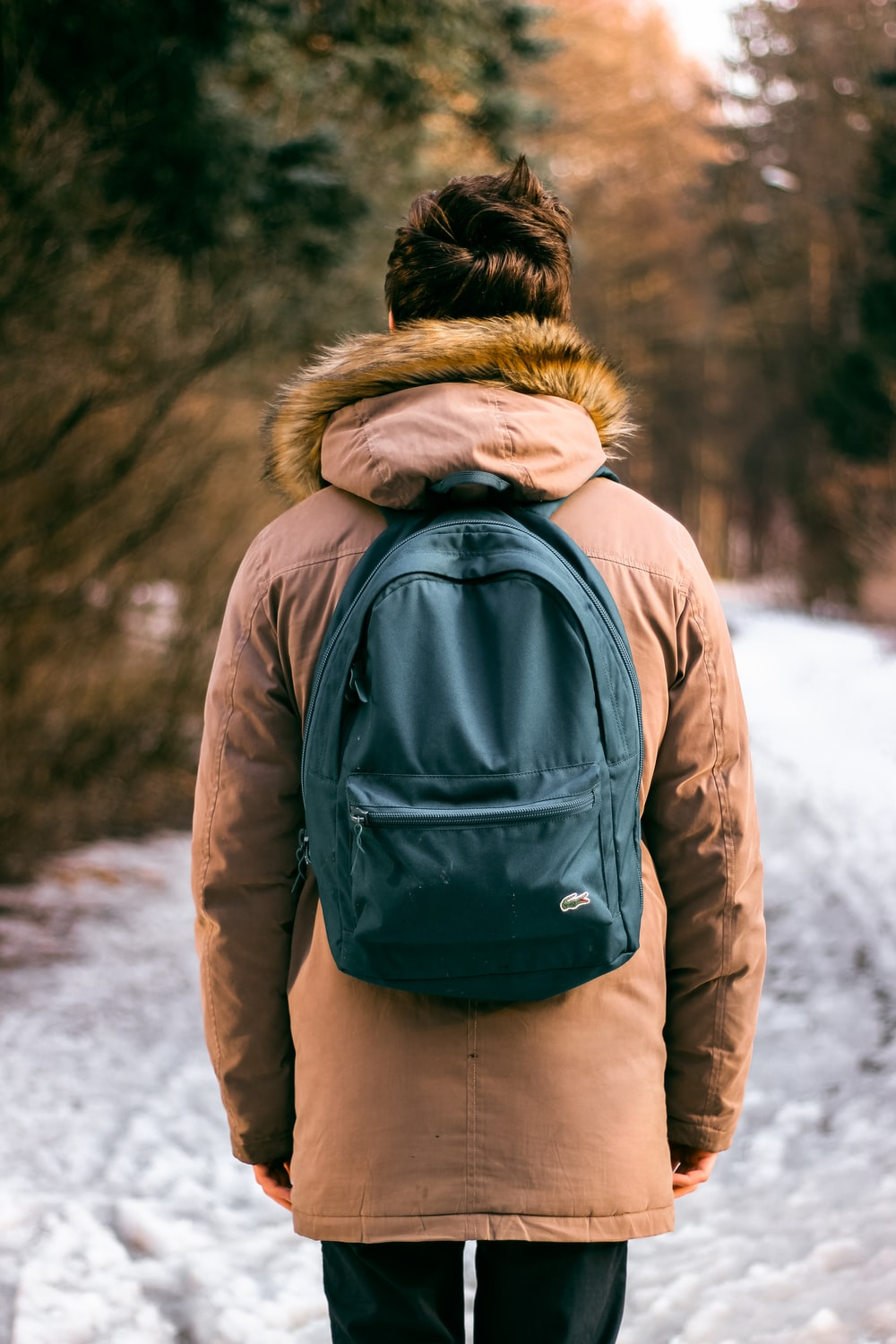 back photo of woman wearing brown parka hoodie and green backpack on snow