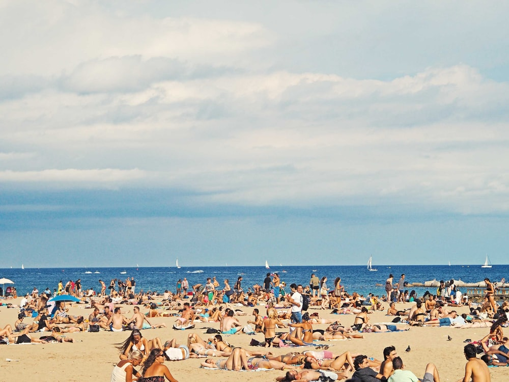Beach is crowded with people on tourism enjoying the summer holiday and vacation in Barcelona