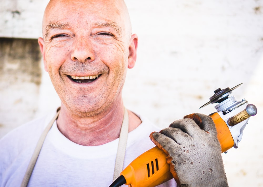 man holding orange angle grinder