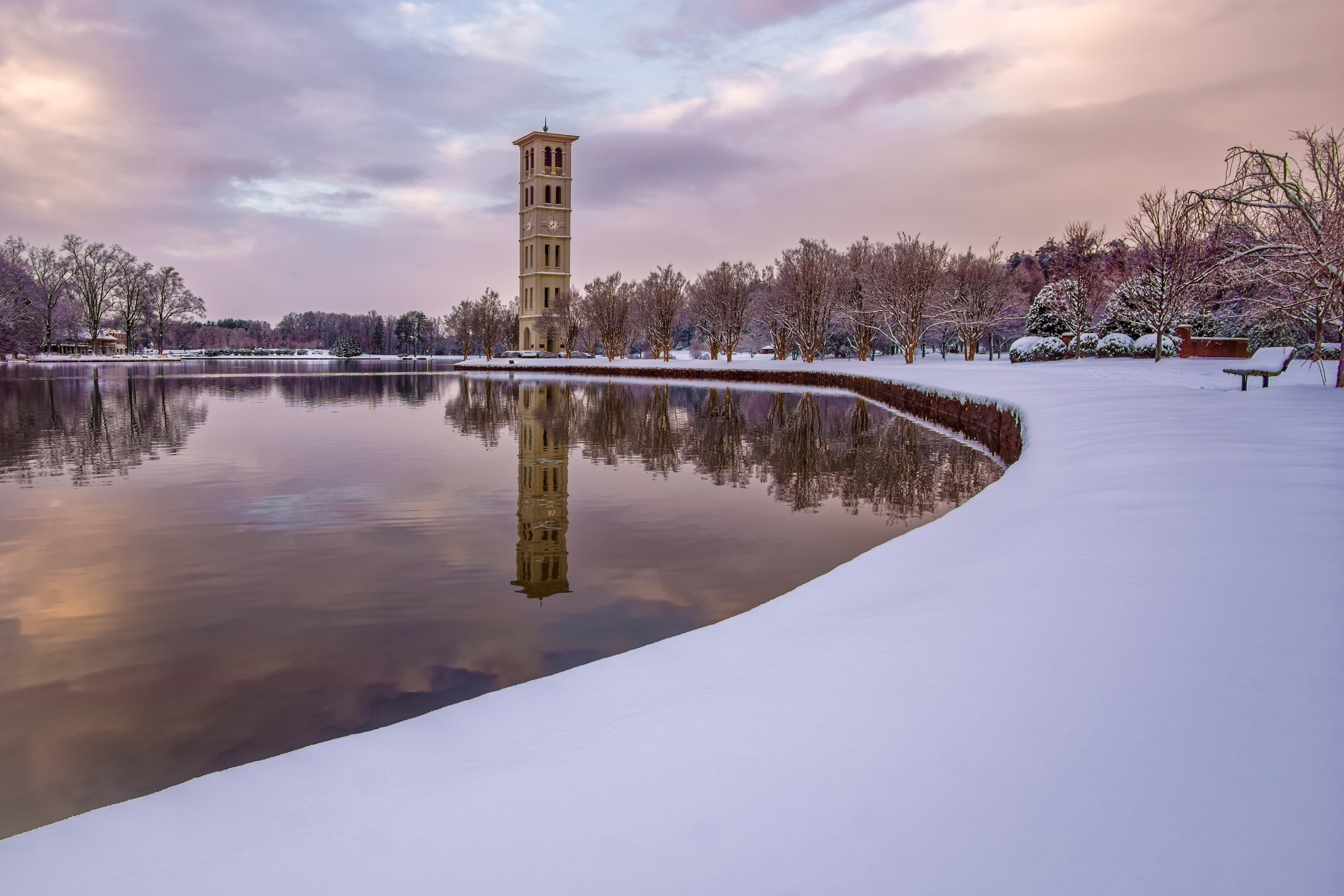 A view of the lake, walking area and sitting bench near Furman University