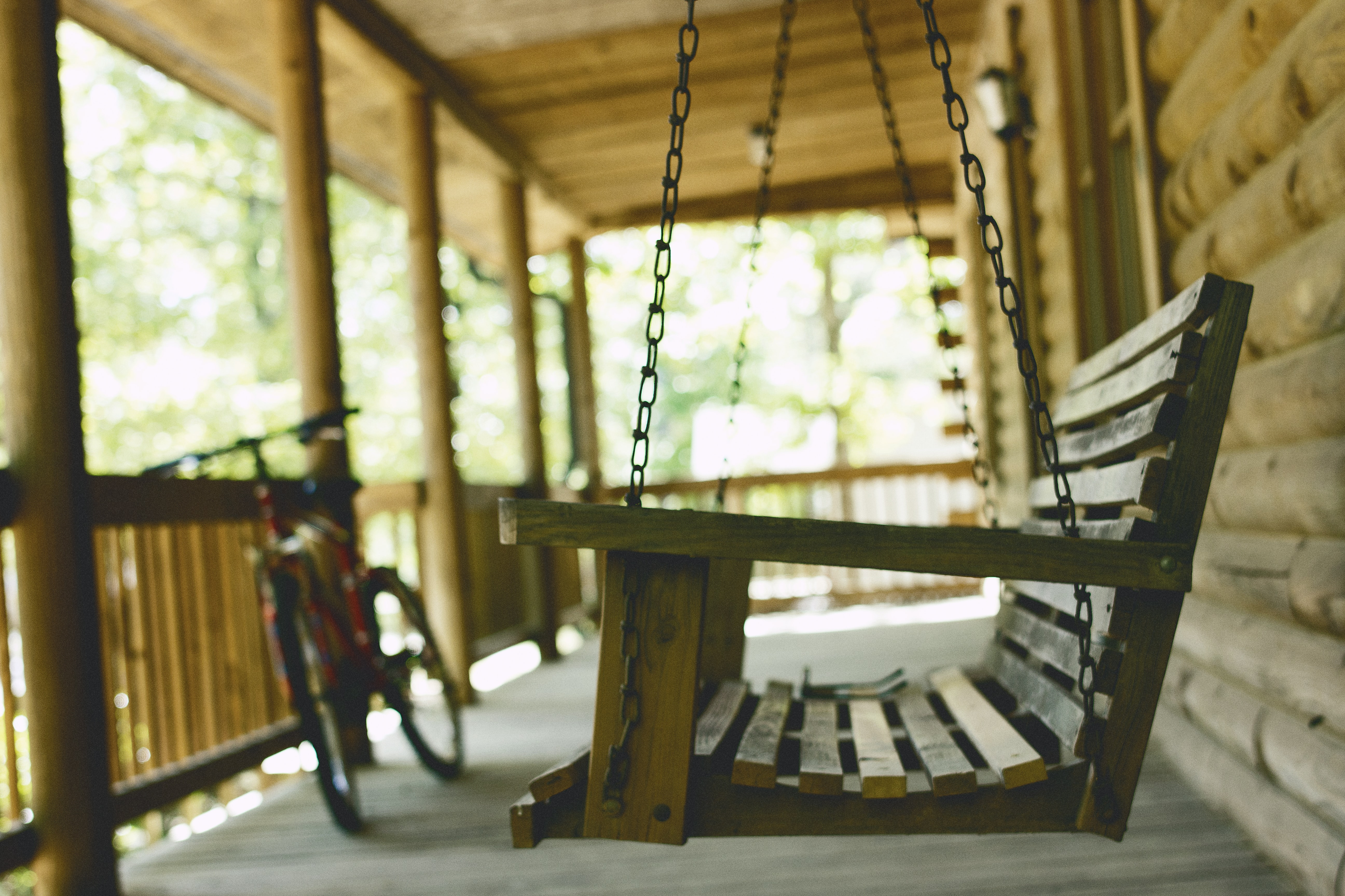 A swing and a bike on the porch of a cabin