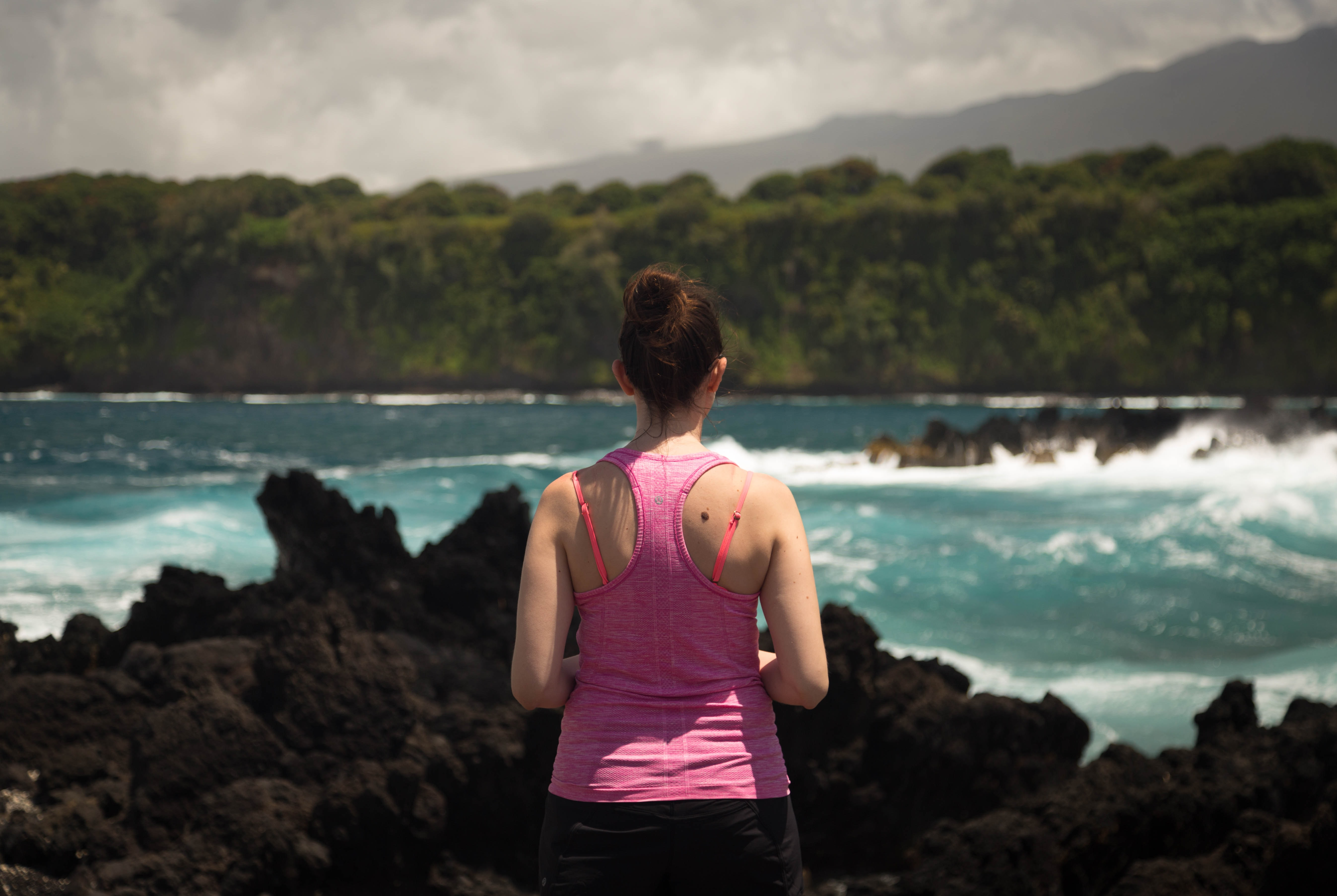 A behind the back shot of a female jogger standing in front of a sea with a beautiful scenic background and clouded sky in Ke'anae