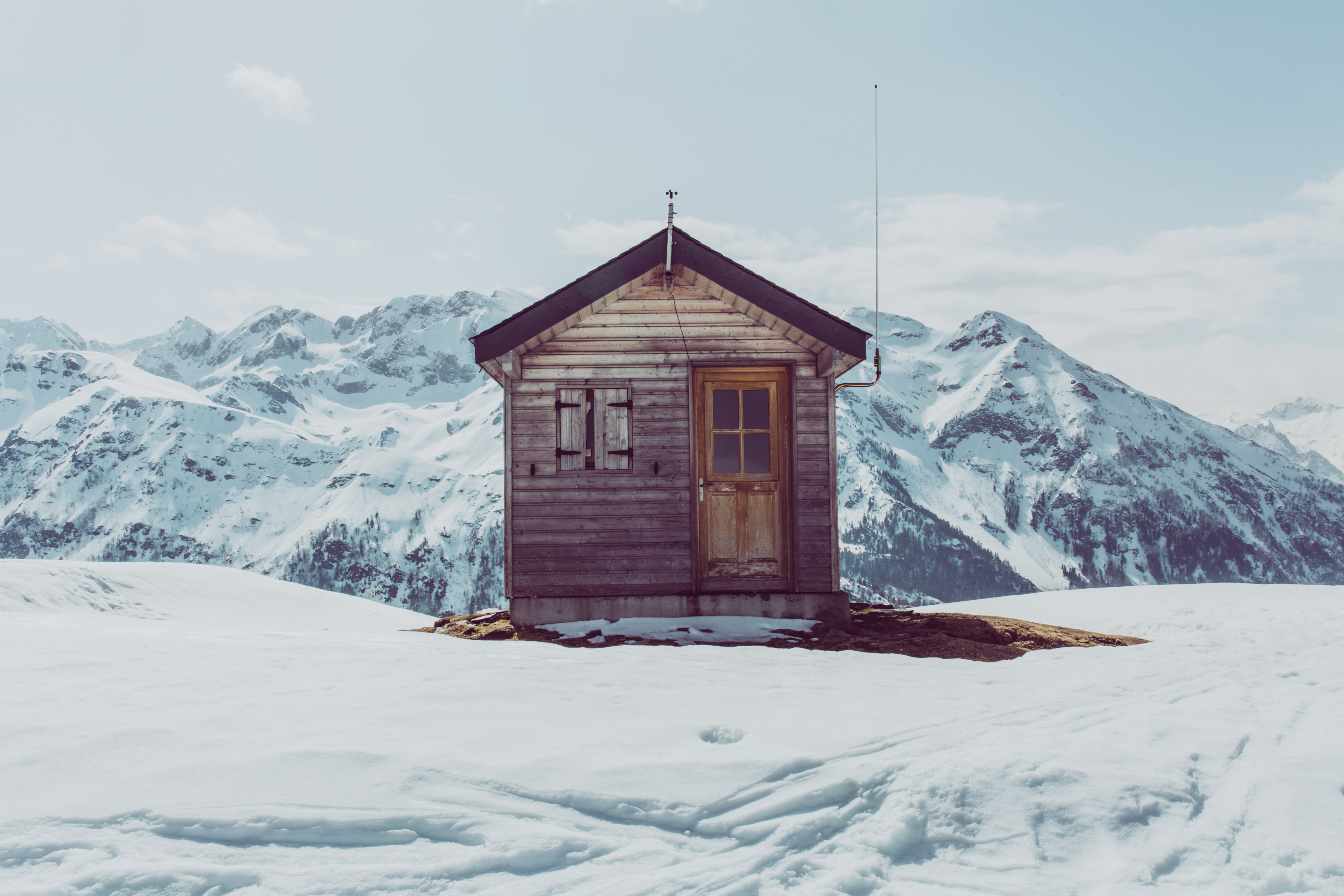 brown wooden house on snow field