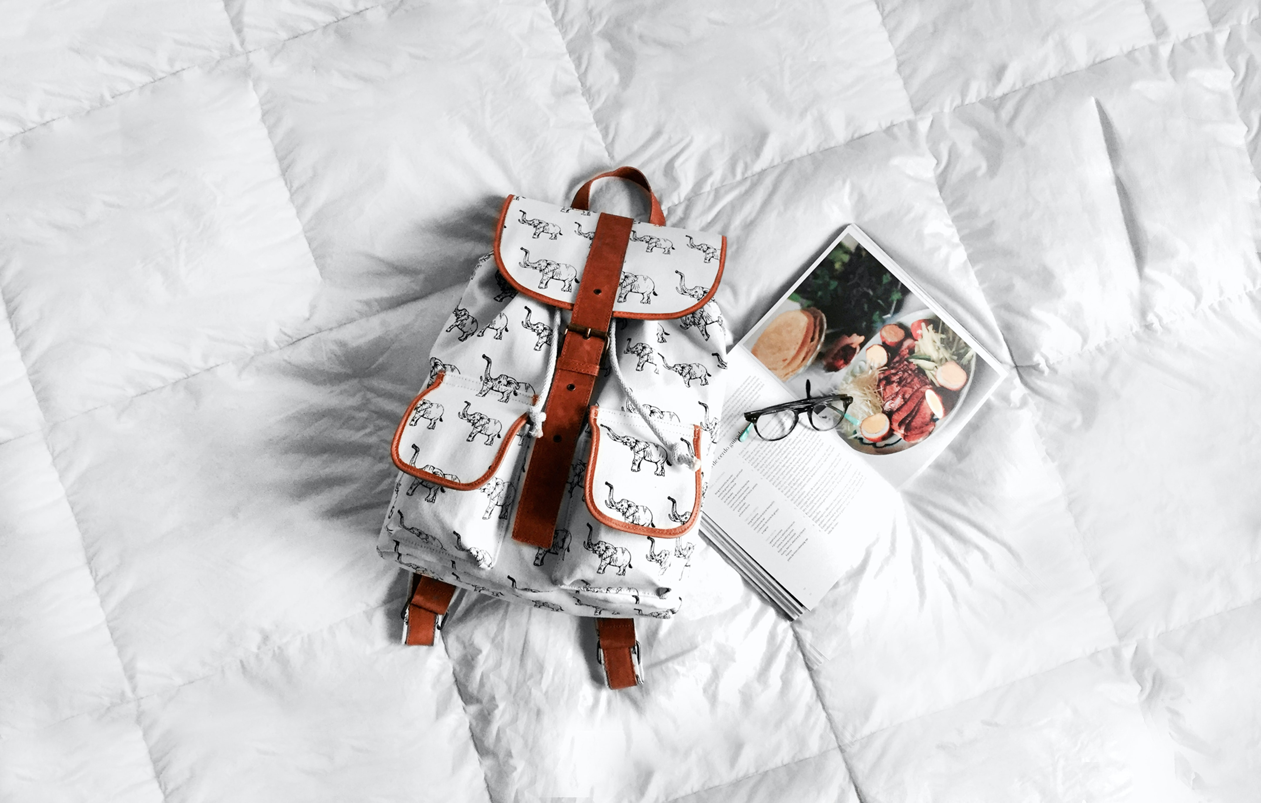 A white backpack on a bed mattress next to a cookbook and a pair of glasses