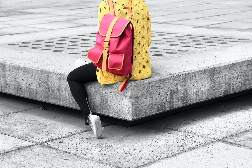 woman carrying pink backpack sitting on the edge concrete bracket