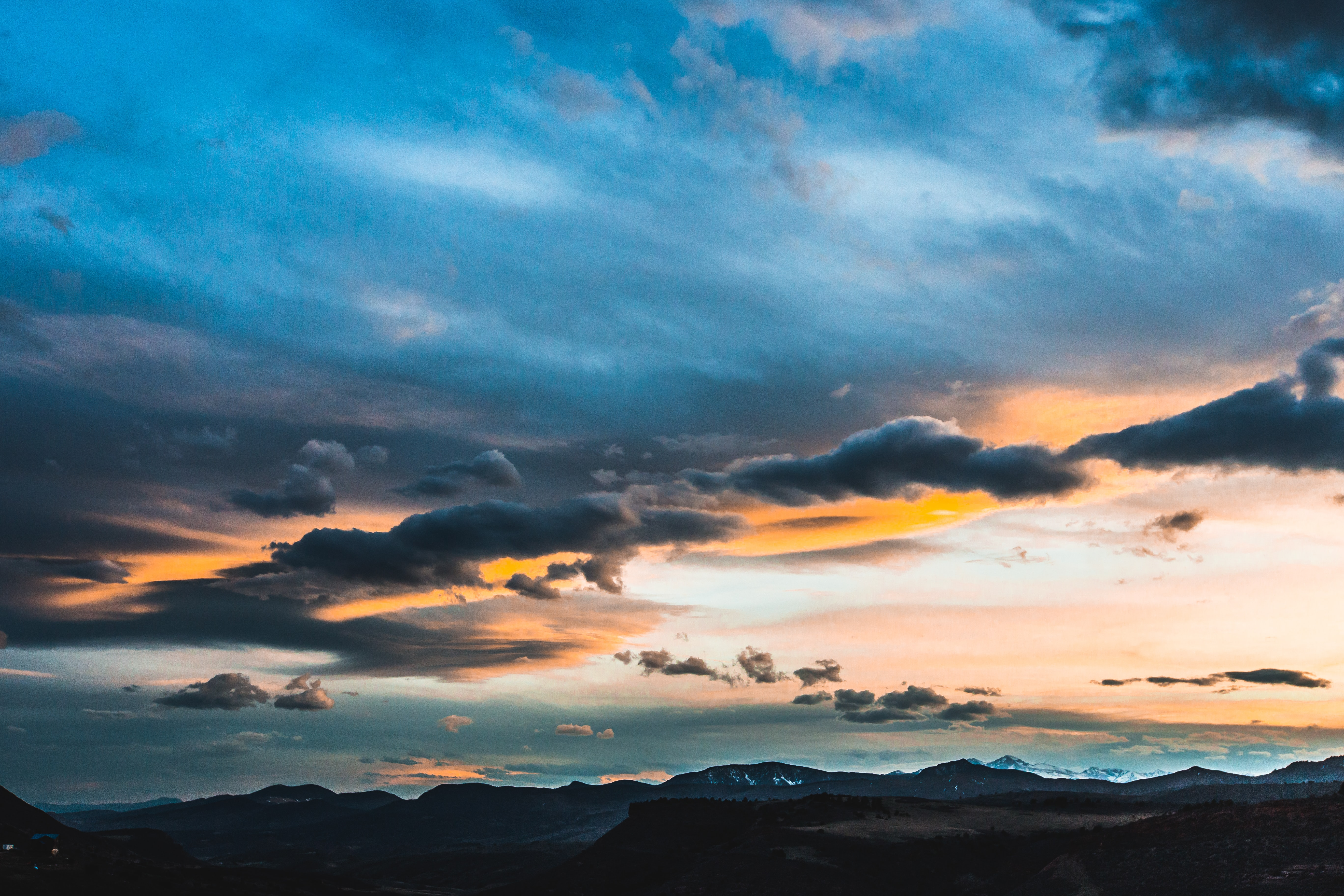 A mountain range at sunset under a cloudy orange sky