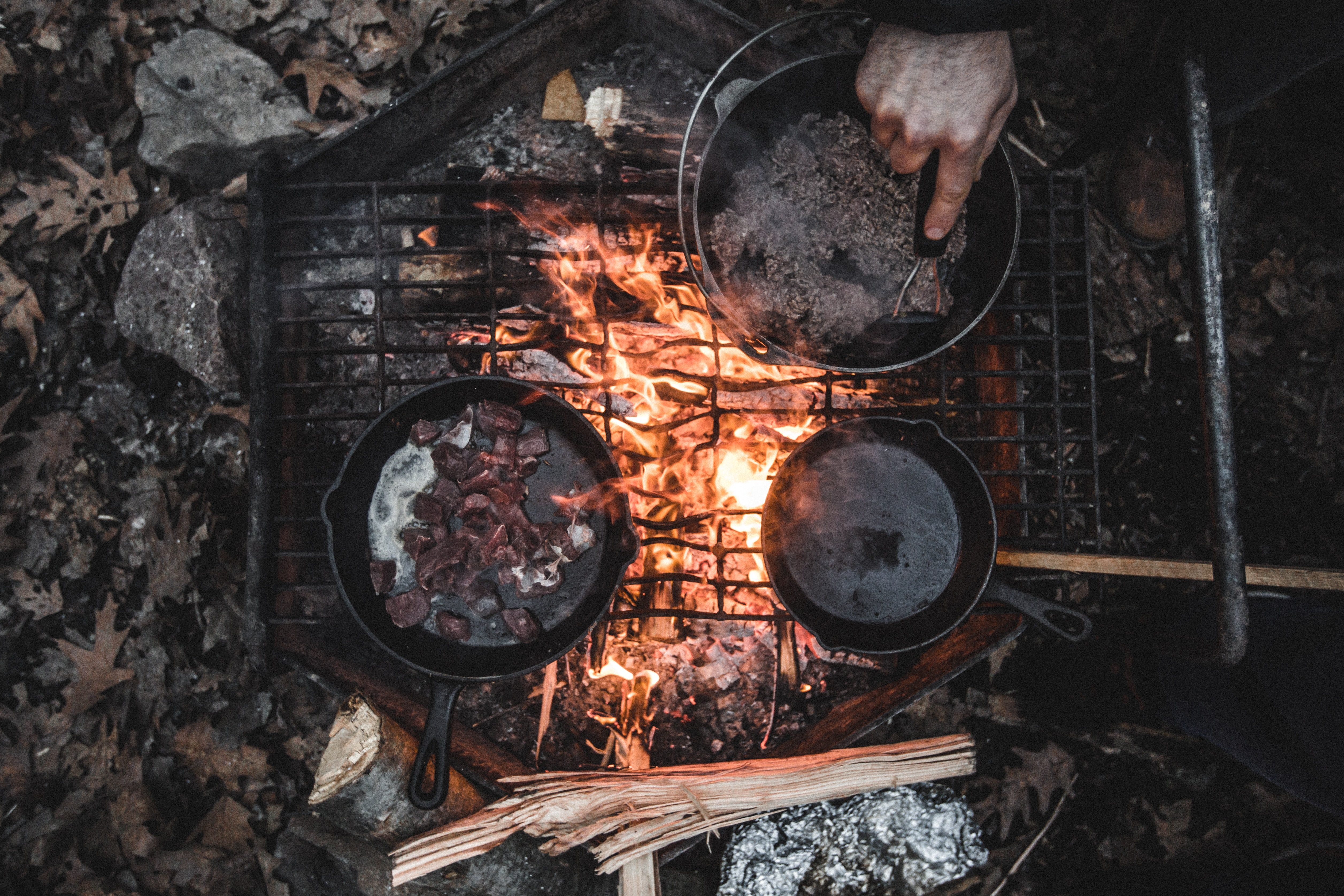 Two cast iron pans and a pot of water over an outdoor fire-lit stove outdoors with a hand mixing the water