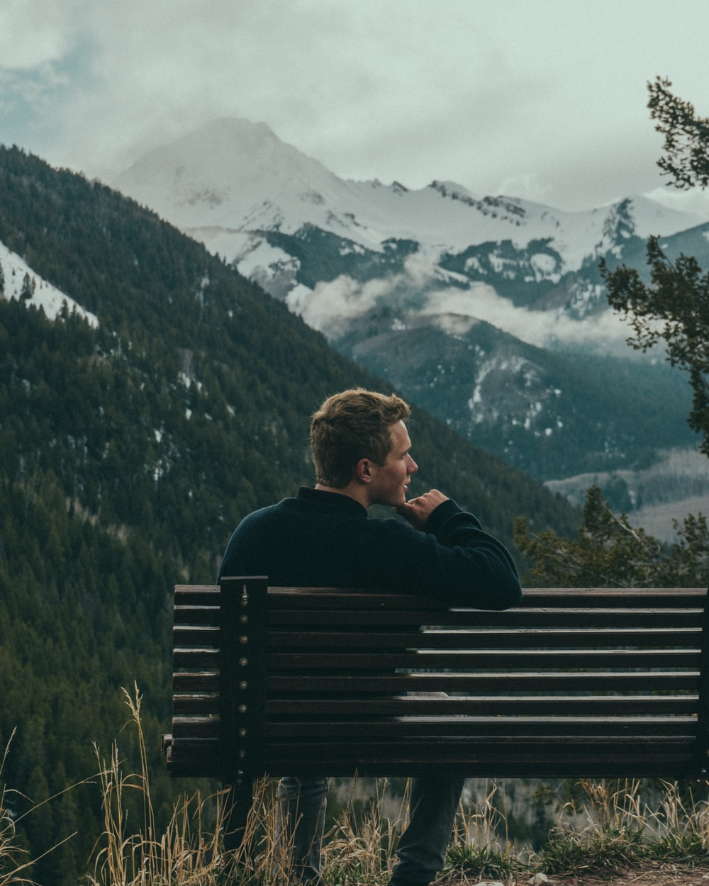 man sitting on bench on top of the mountain