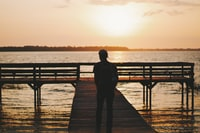 silhouette of man walking on dock during golden hour