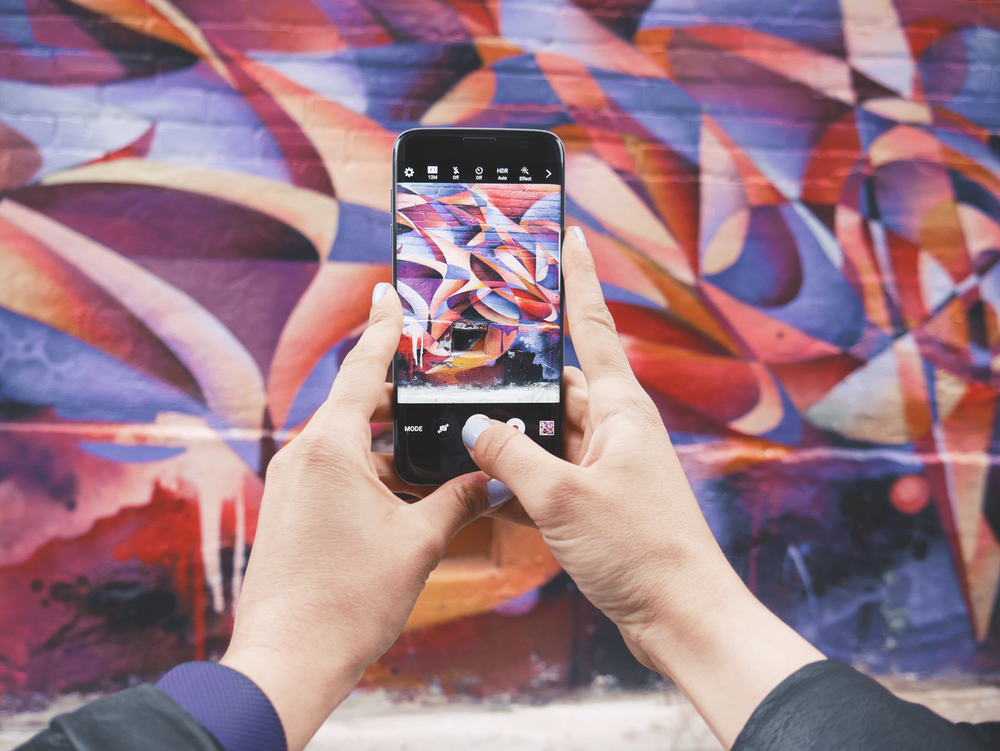 person holding Android smartphone and taking a photo of abstract wall during daytime