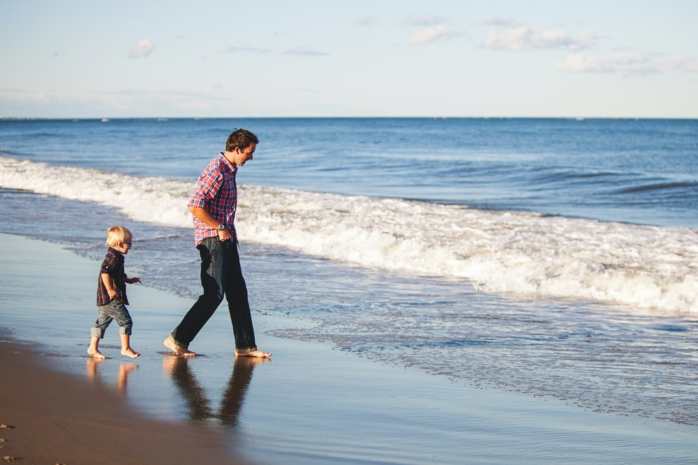 Father and son walking into ocean barefoot at Seabrook Beach