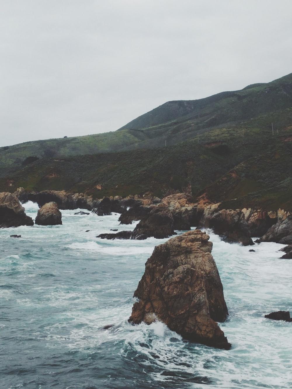 brown rock on body of water near mountain