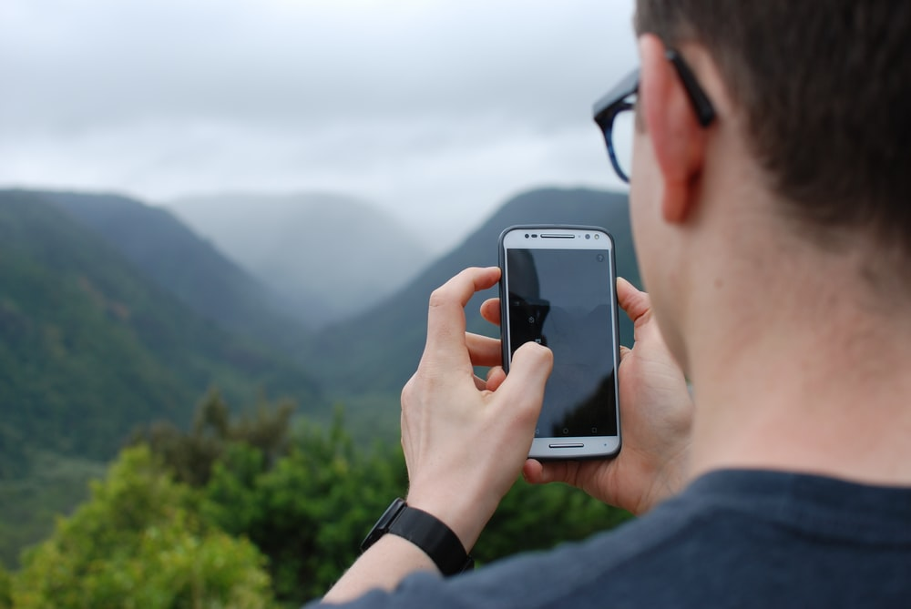 person taking photo of hills during daytime