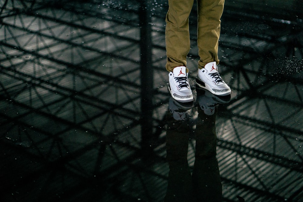 person wearing white-and-gray Air Jordan 3 standing on black tinted glass
