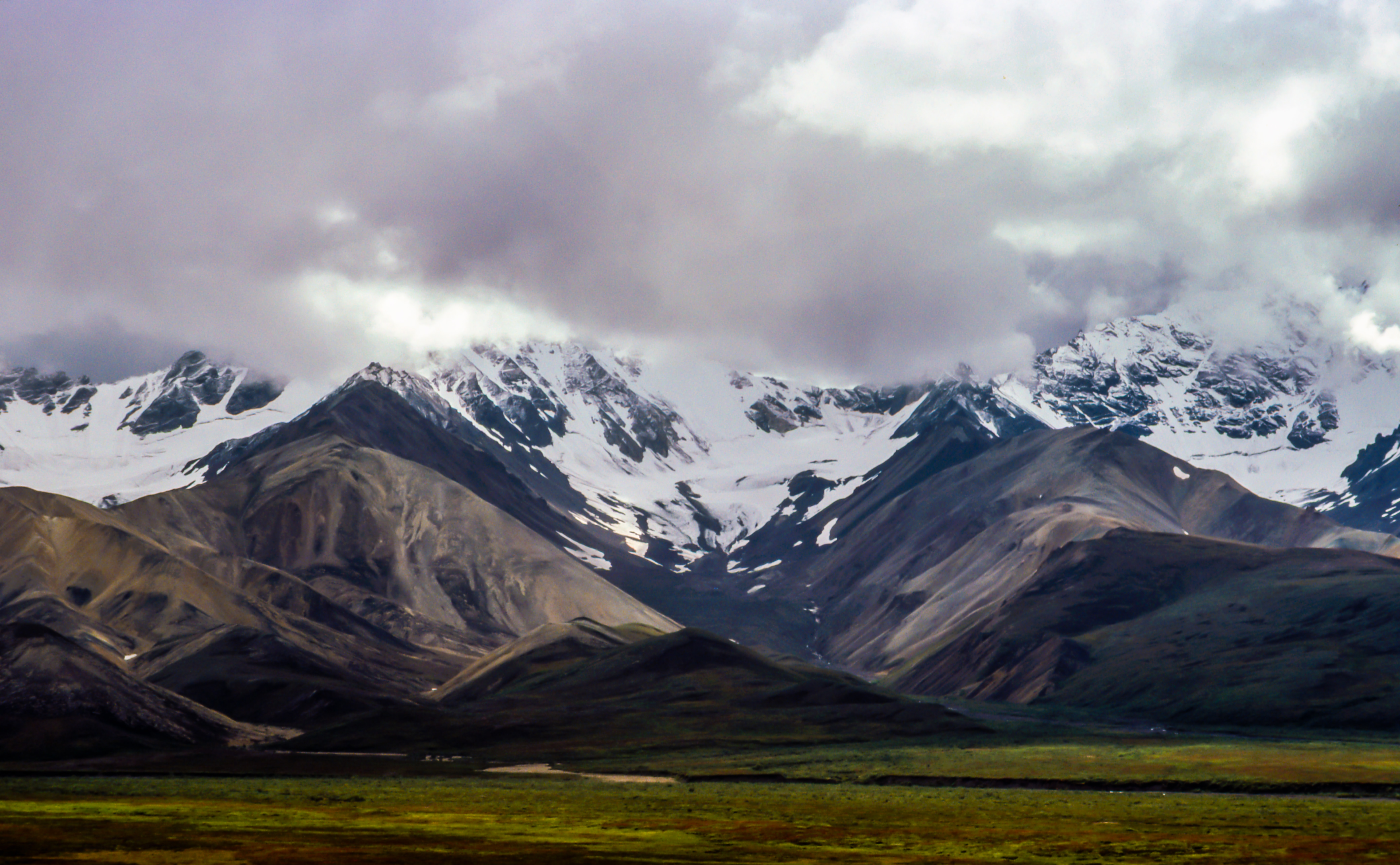 Heavy clouds hover over a snow topped mountain range