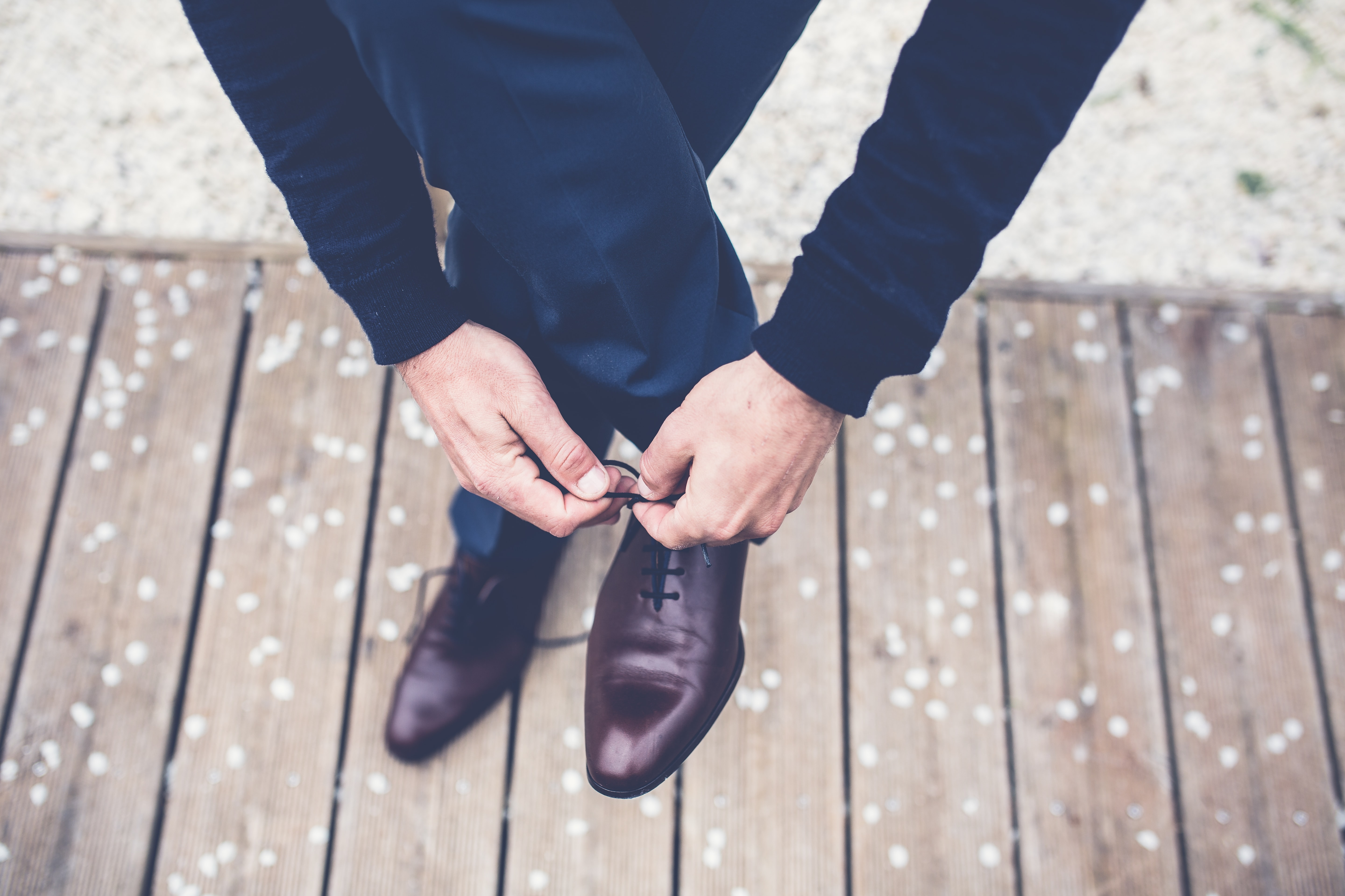 A man in a navy blue suit tying his brown leather shoes