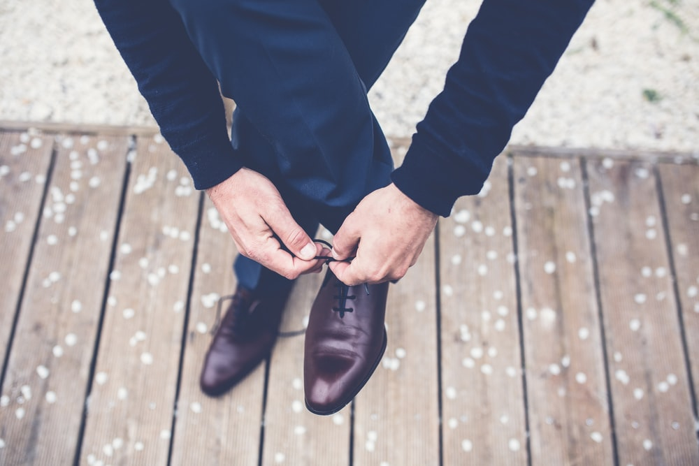 person tied dress shoes