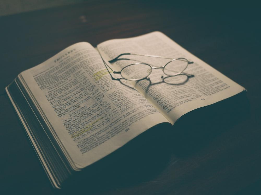 gray framed eyeglasses on open book