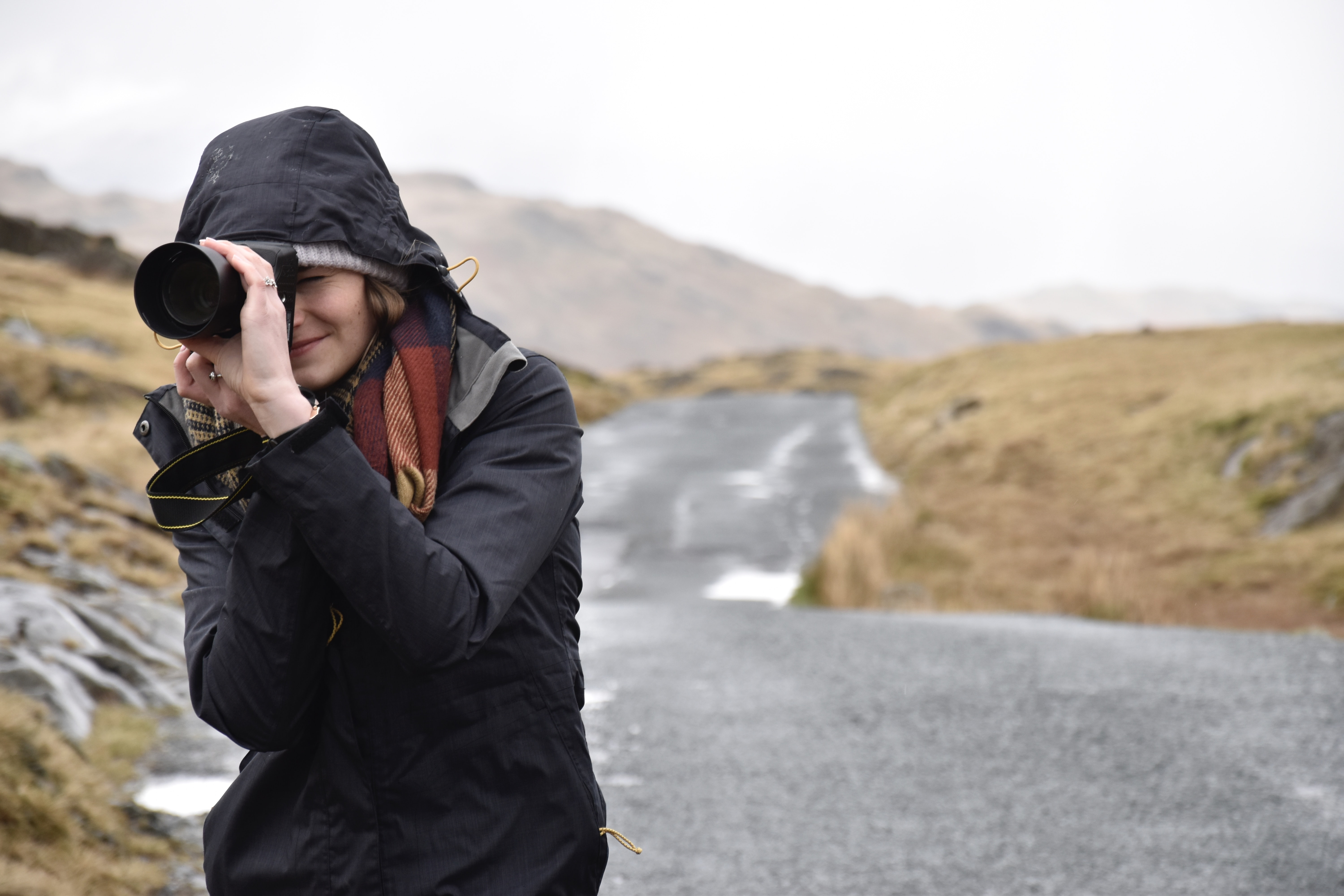 Photographer focuses her camera lens on a mountain road