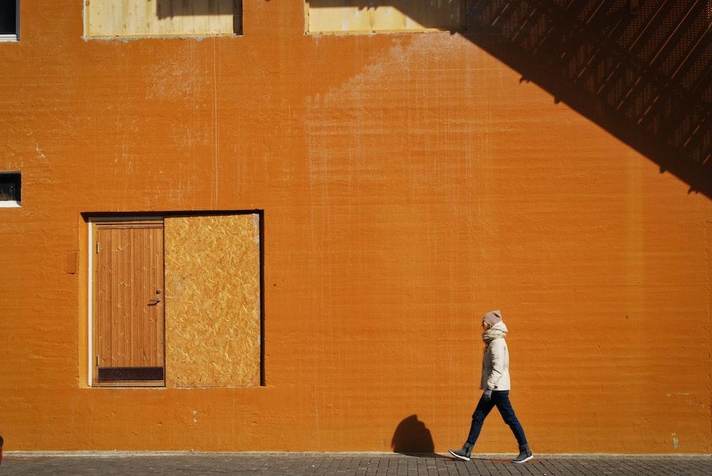 man walking beside orange building at daytime