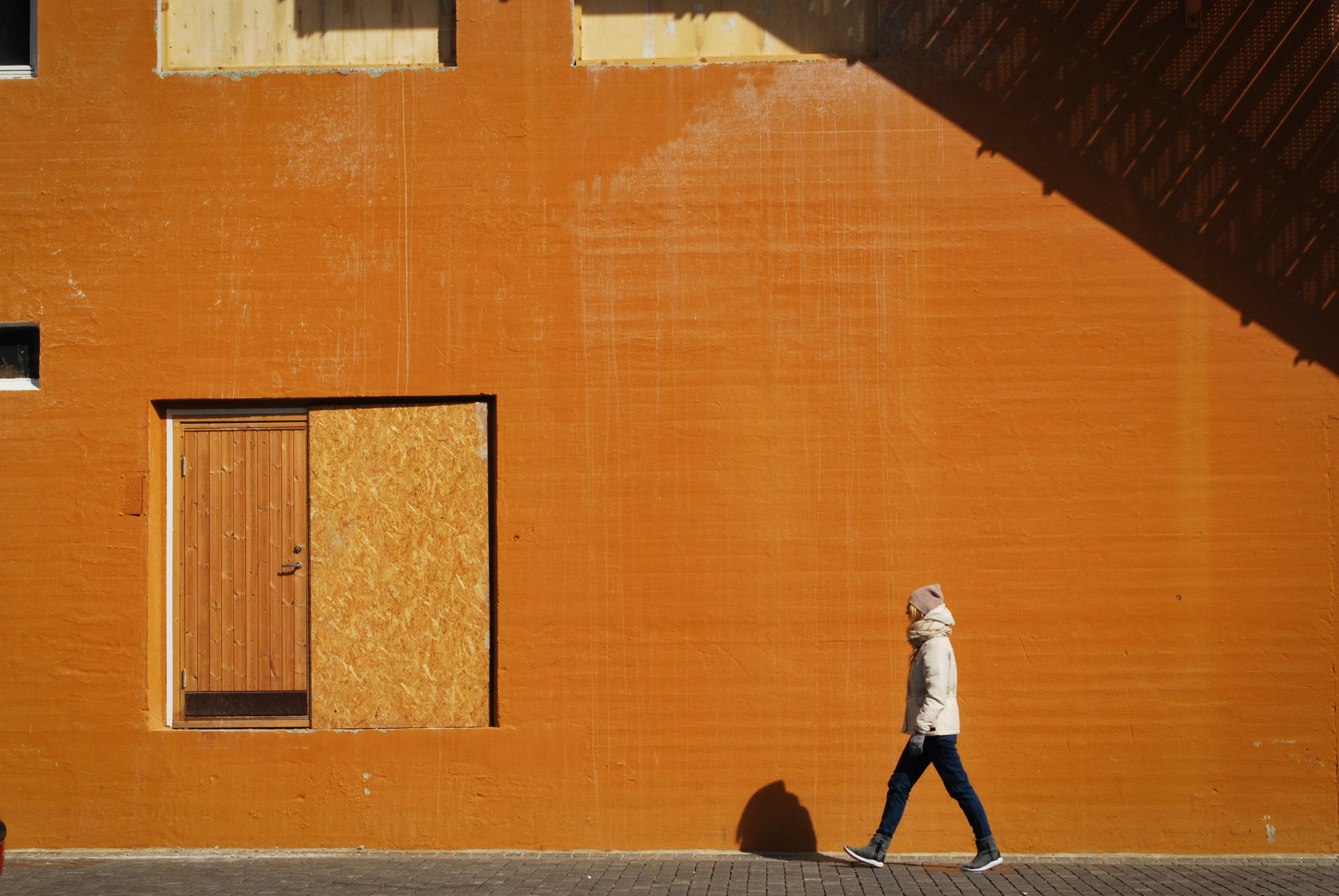 man walking beside orange building at daytime