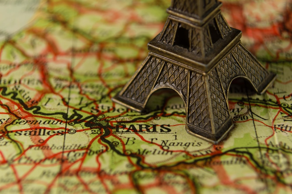 A macro shot of an Eiffel Tower figurine on top of a map of Paris