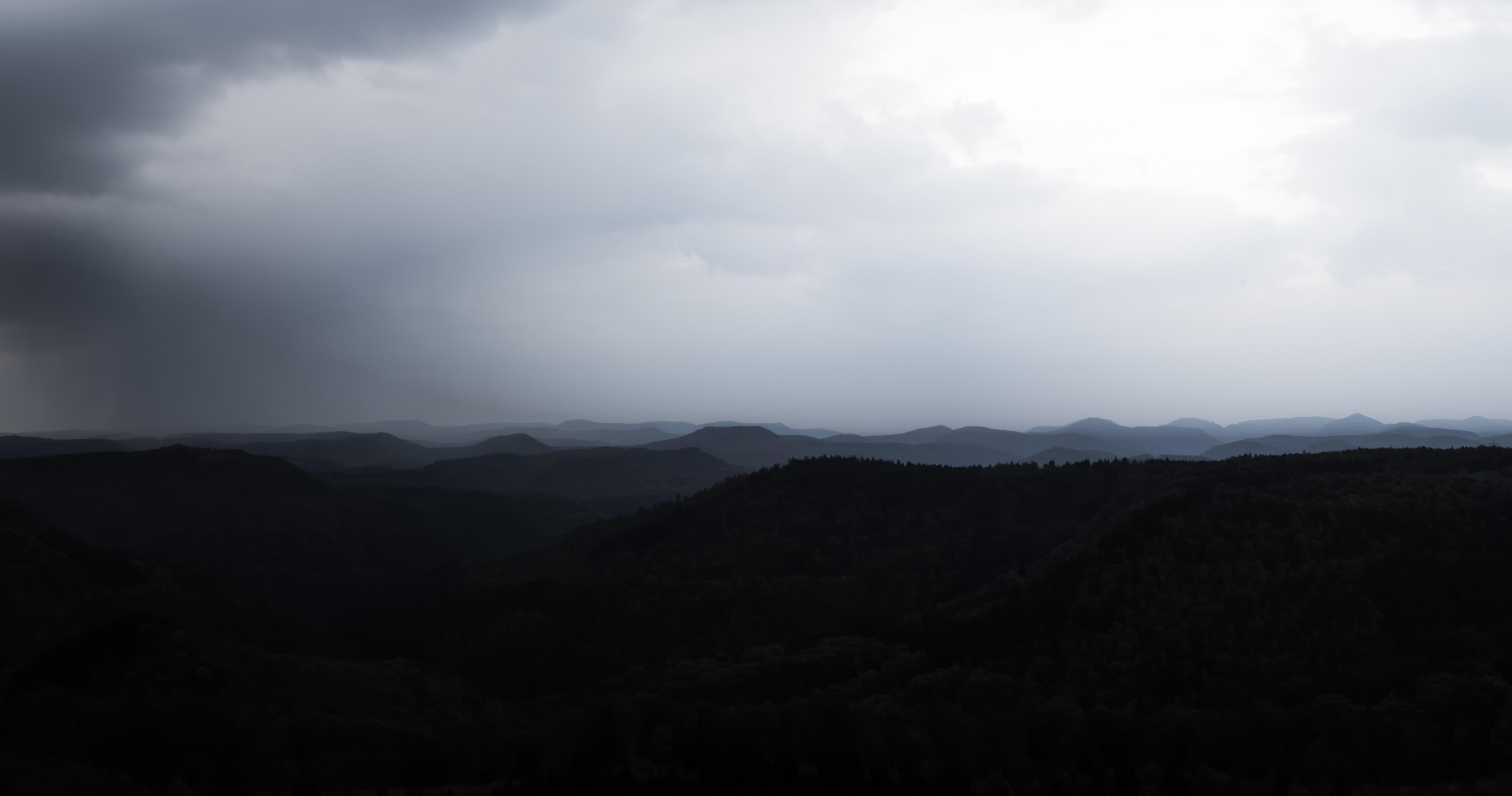 Gloomy silhouette of a mountain ridge on a foggy day