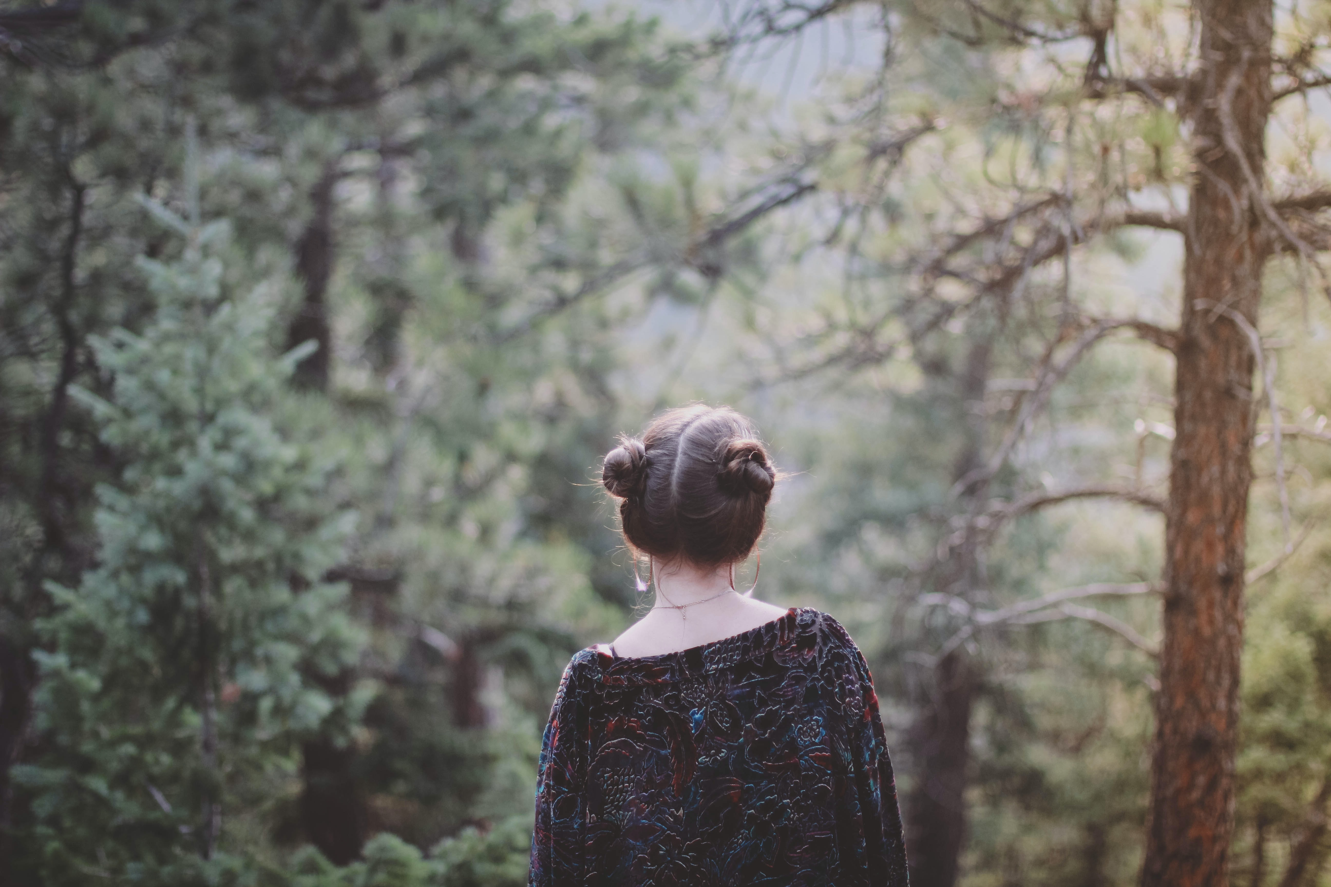 A woman with her hair up in buns walking through an evergreen forest