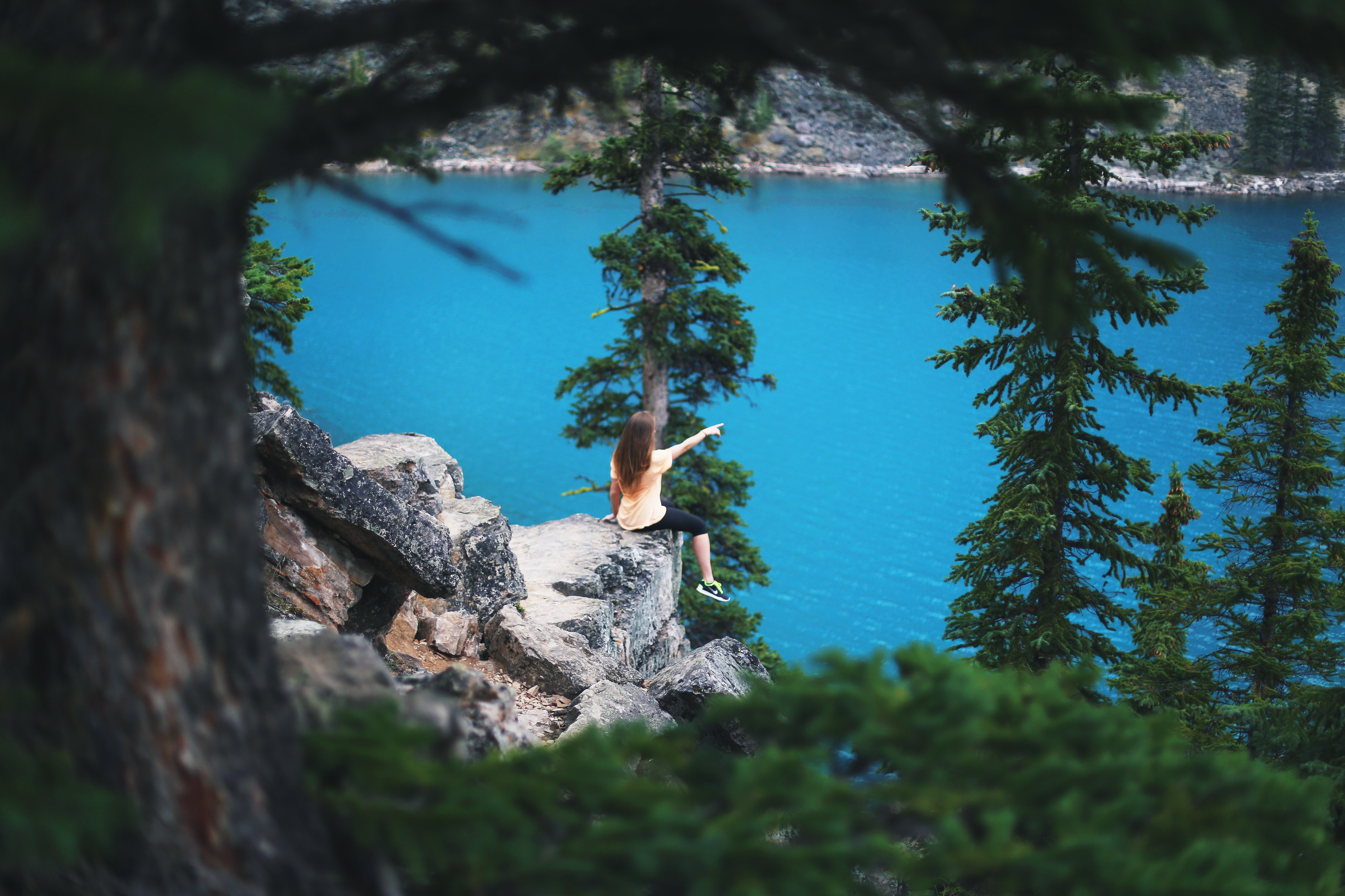 A young woman with an outstretched arm seated on rocks overlooking the azure Moraine Lake