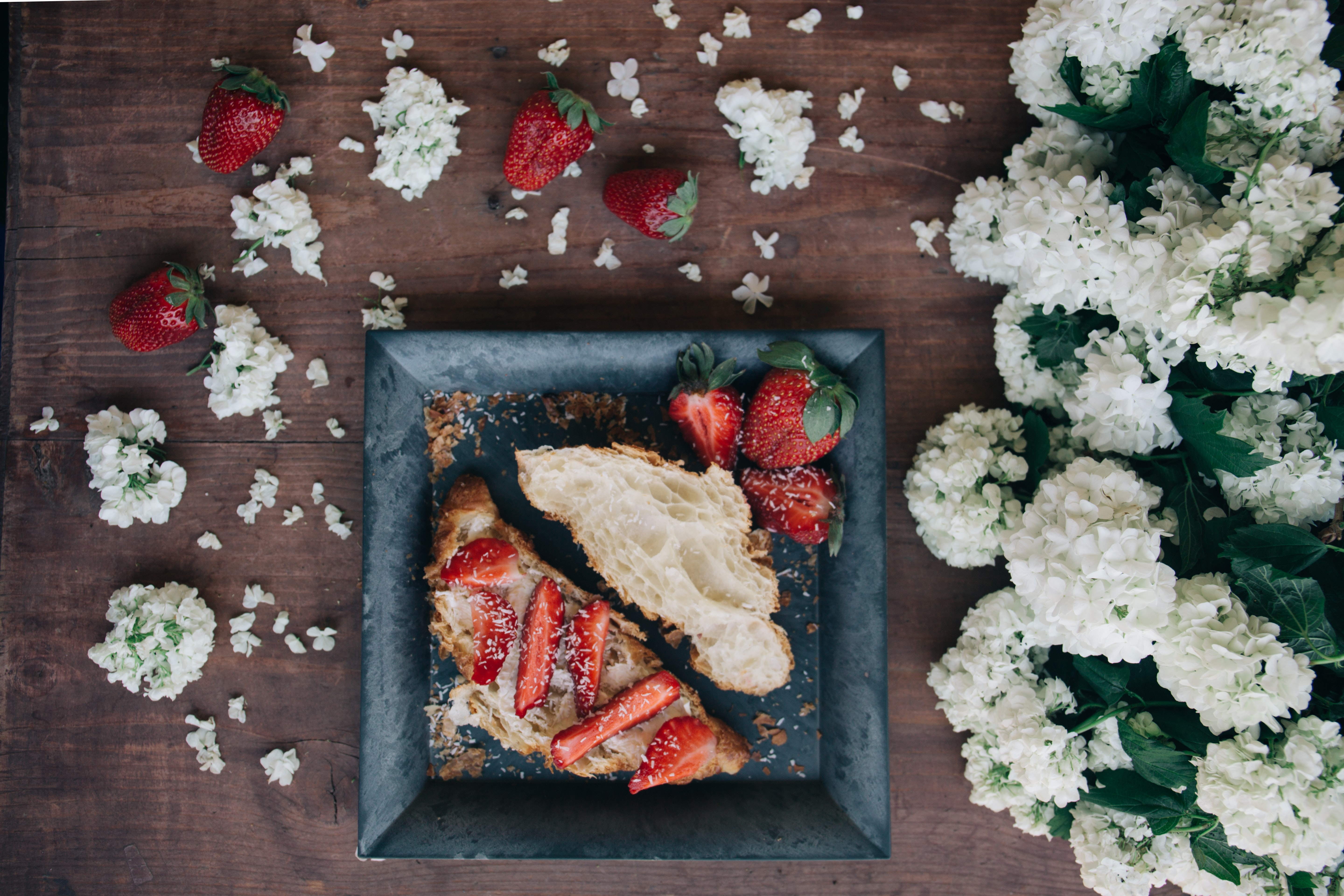 Croissant with powdered sugar and strawberries surrounded by flowers