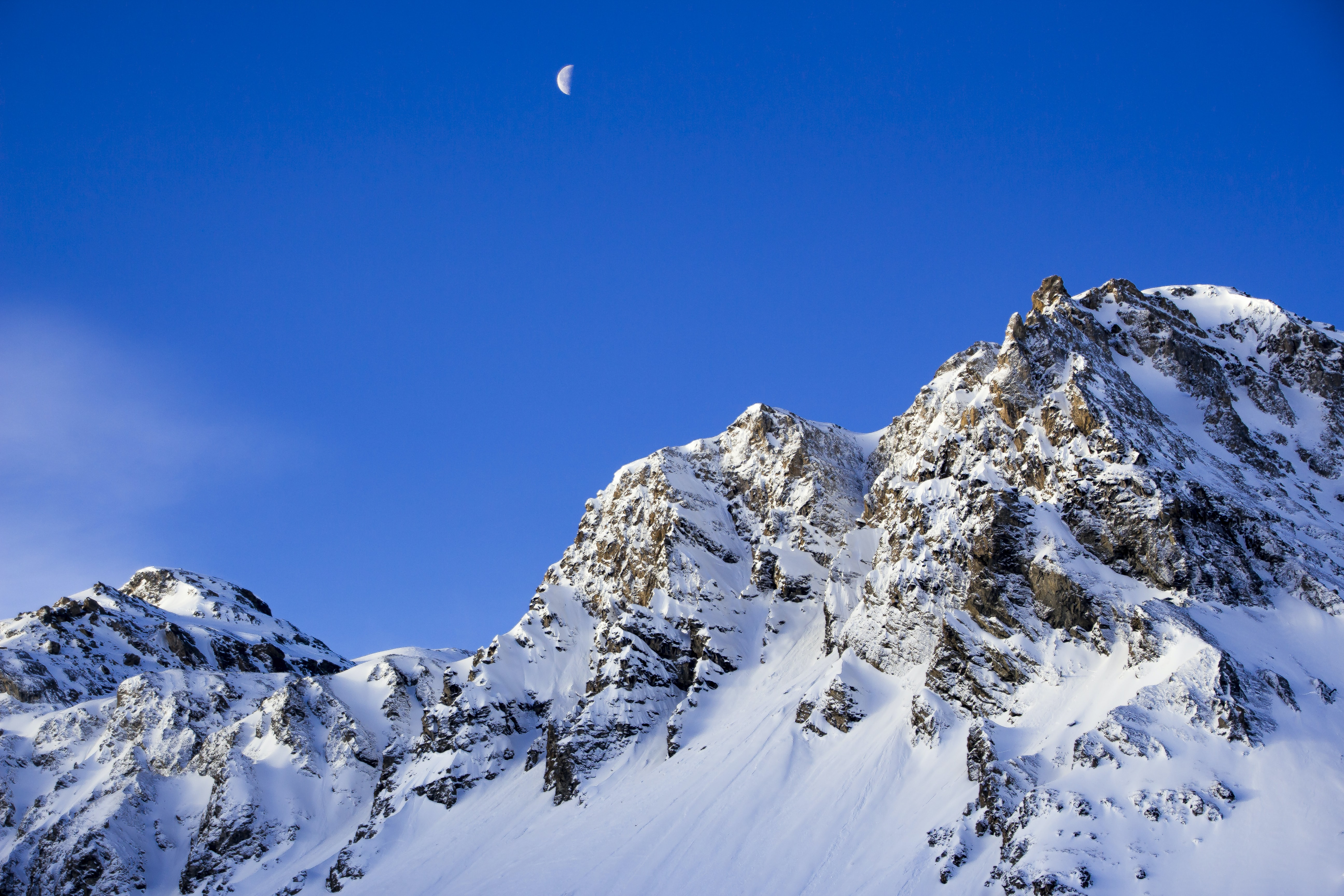 Half moon rises over the snow covered mountains in France