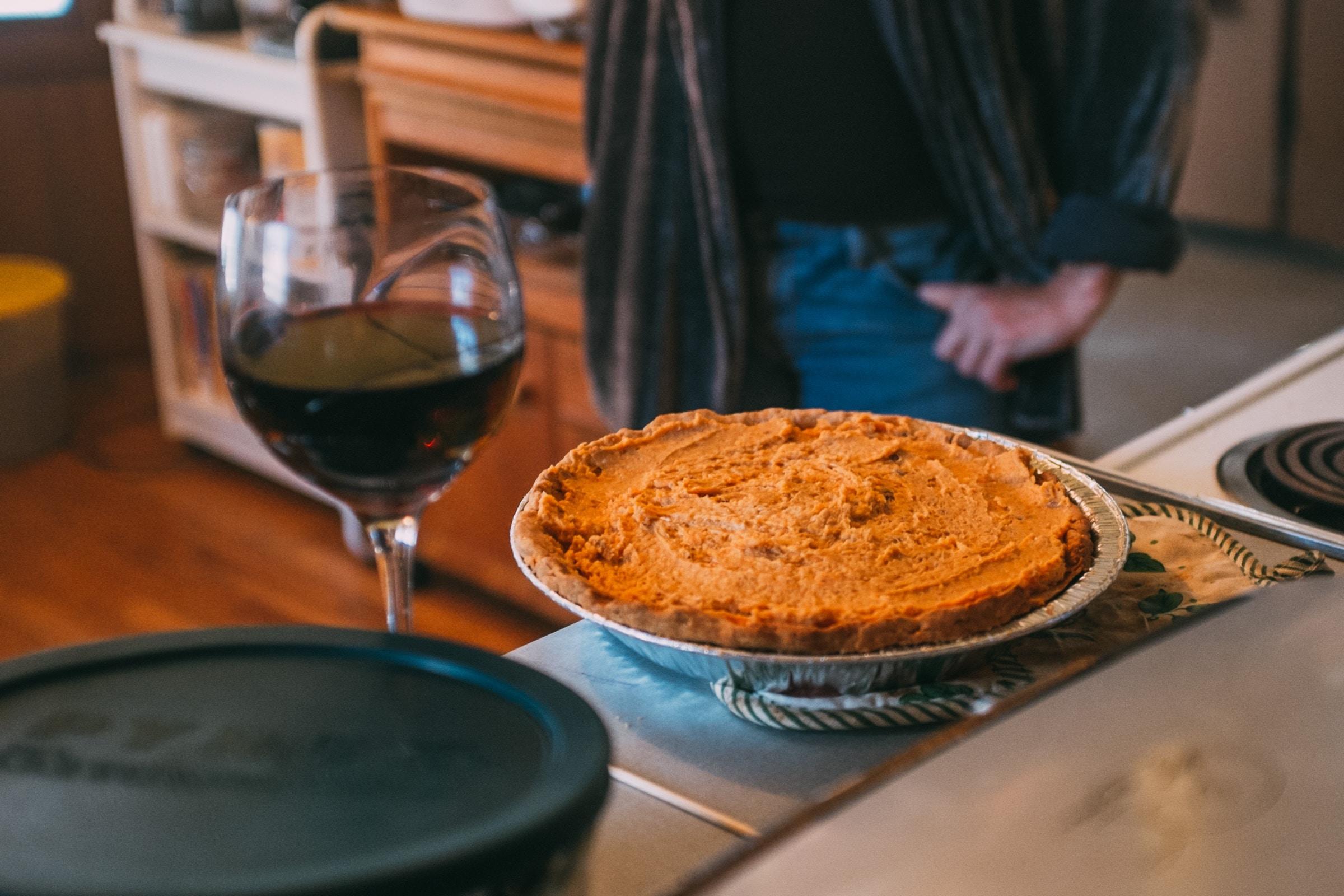 A pie next to a glass of wine.