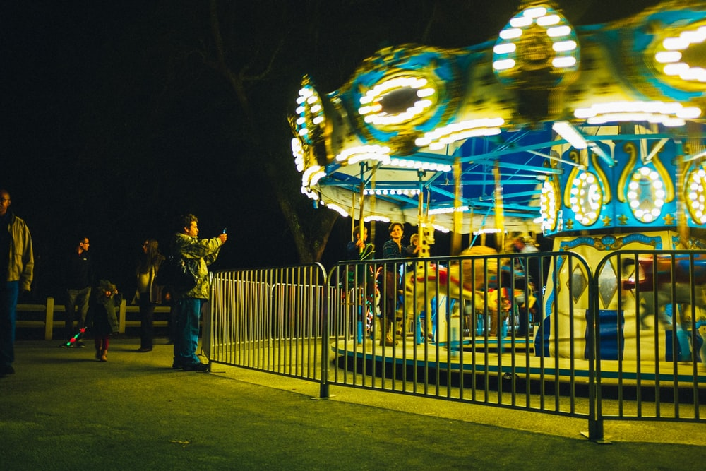 people standing near white and blue carousel during night time