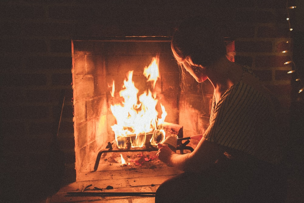 man in white and black checkered dress shirt sitting in front of bonfire