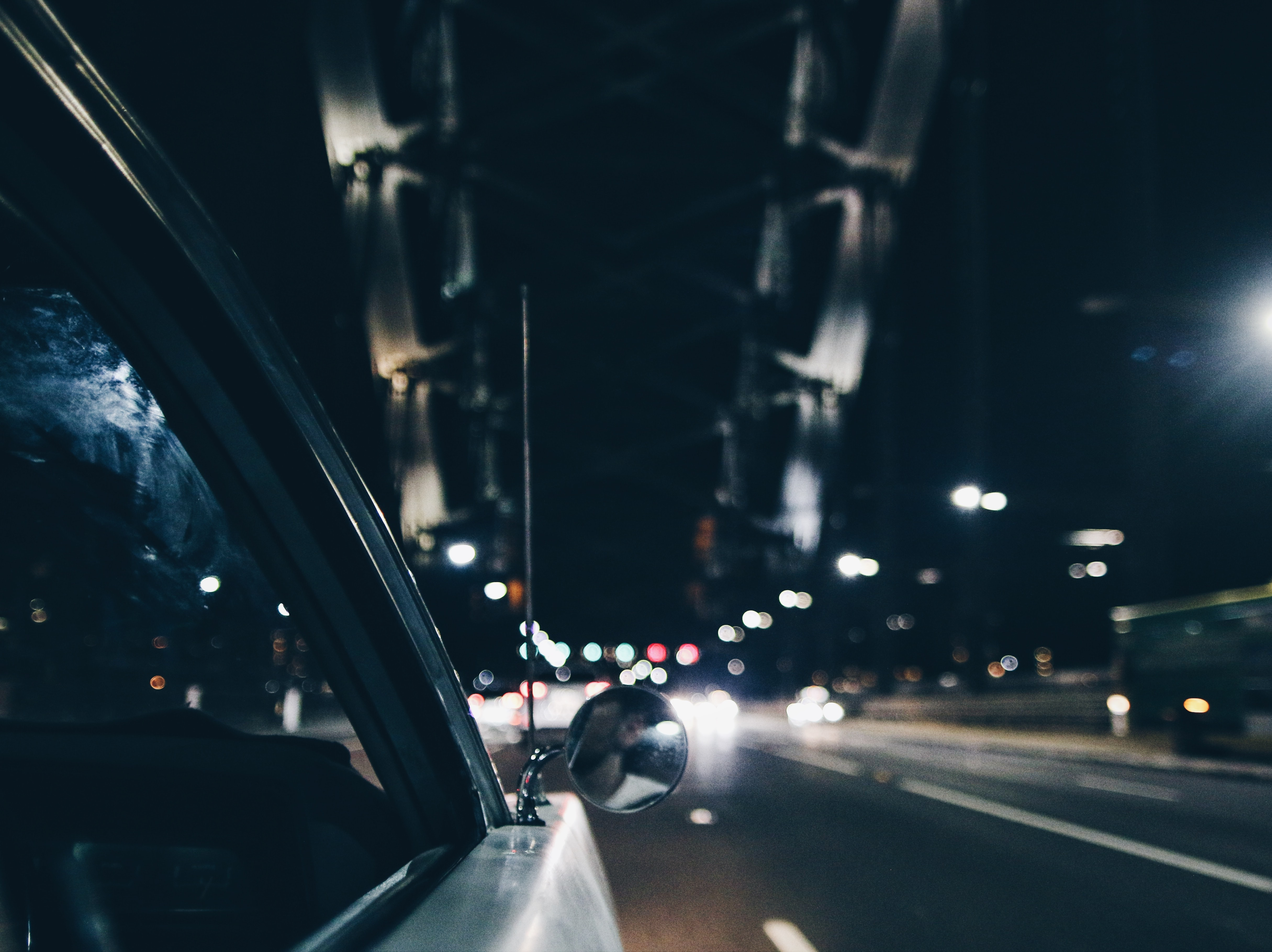 The view from the side of a car on a bridge at night with bokeh effect