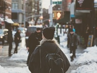 woman carrying backpack standing beside snow on street at daytime