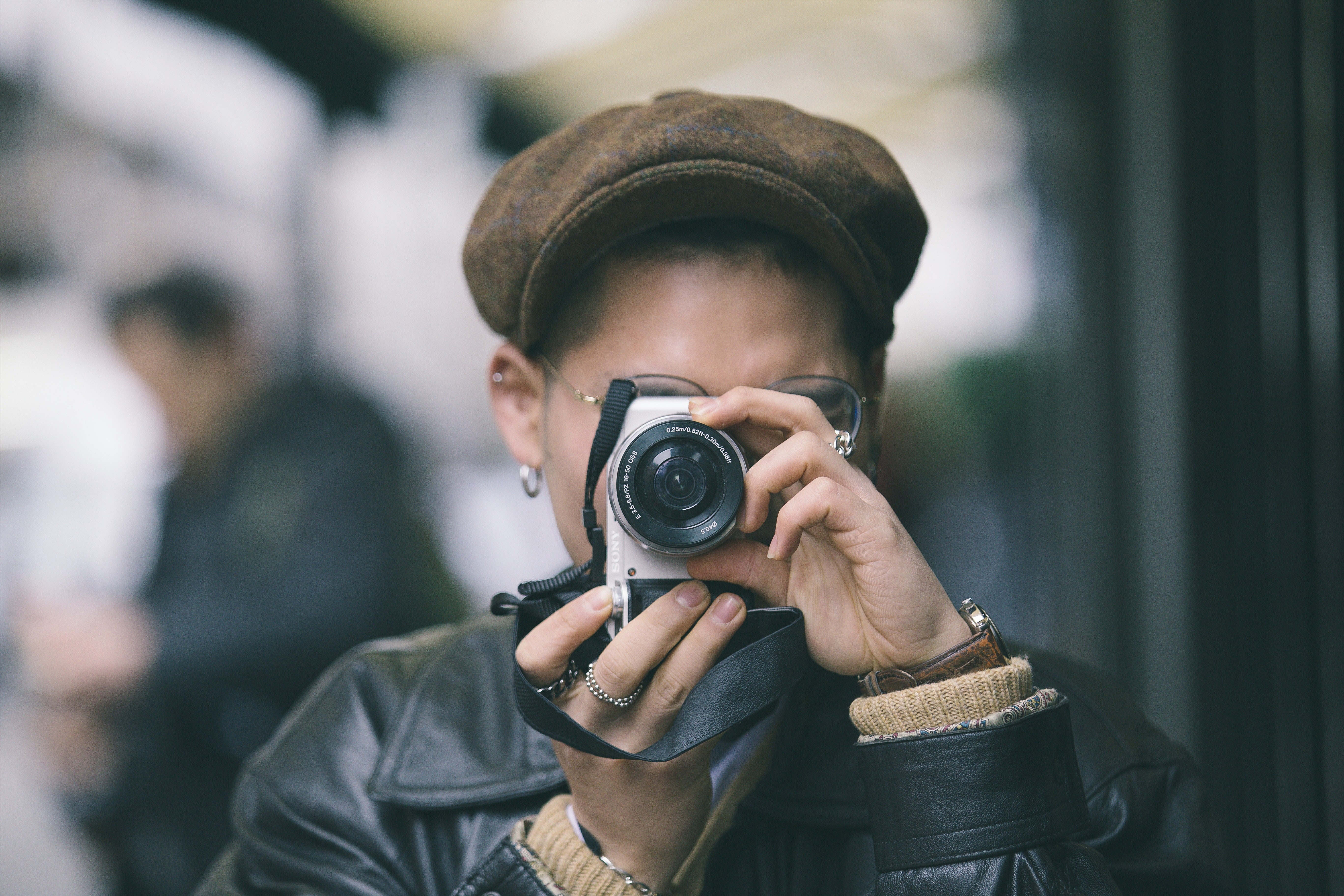 A person wearing a hat taking a photo with a white Sony camera on Brewer Street